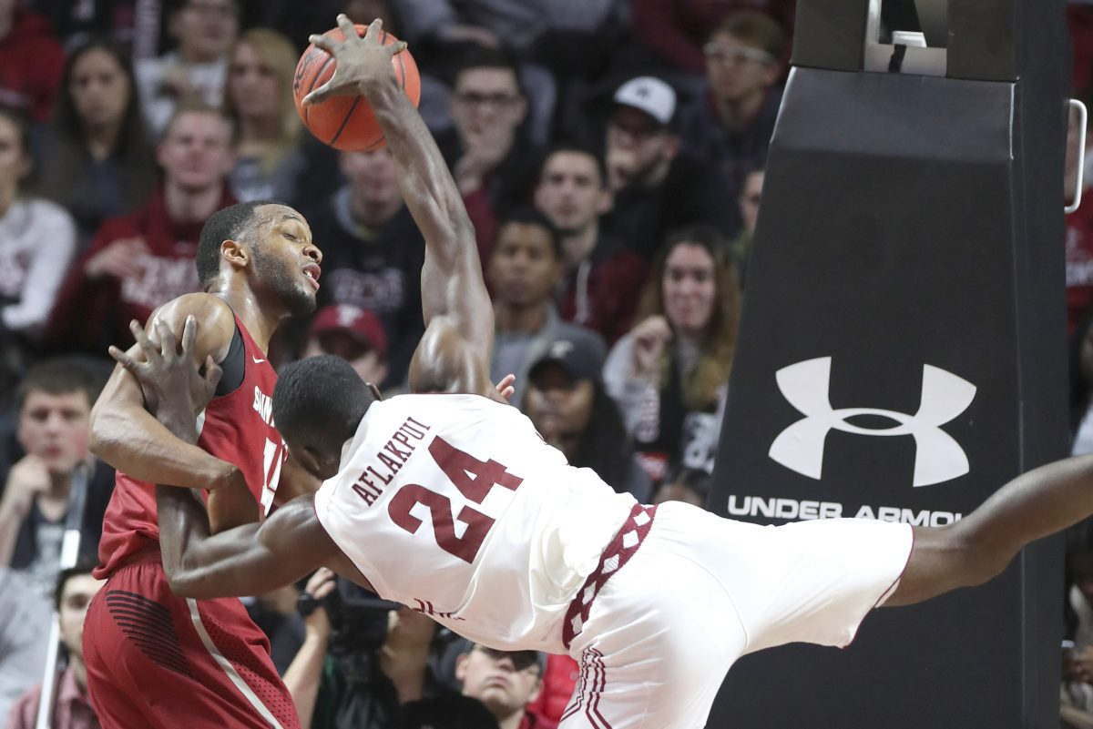 Chris Clover of St. Joseph´s fouls Ernest Aflakpui of Temple to prevent a layup during 2nd half action at the Liacouras Center on Dec. 9, 2017. CHARLES FOX / Staff Photographer