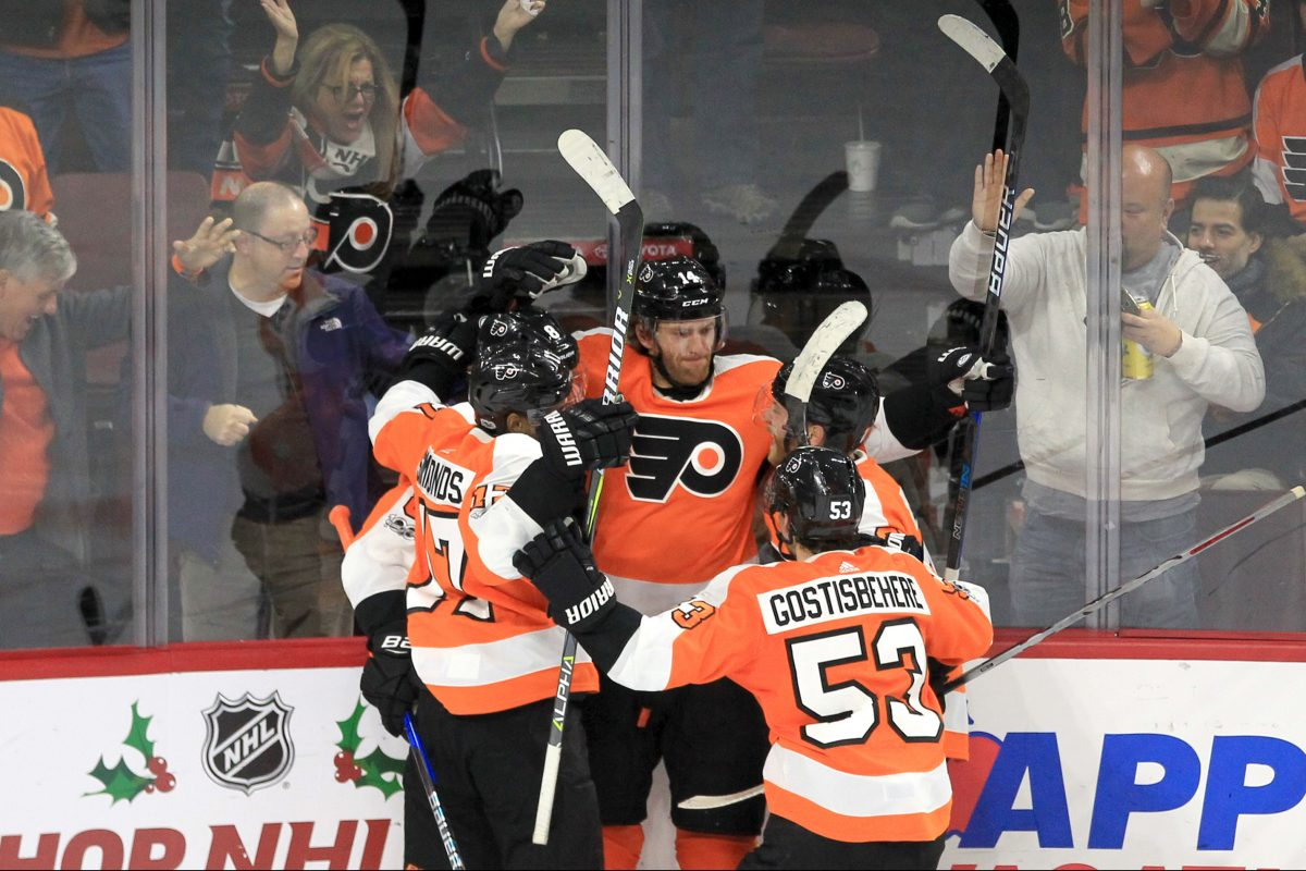 The Flyers' Sean Couturier, center, is swarmed by teammates after his goal broke a 2-2 deadlock against the Maple Leafs.