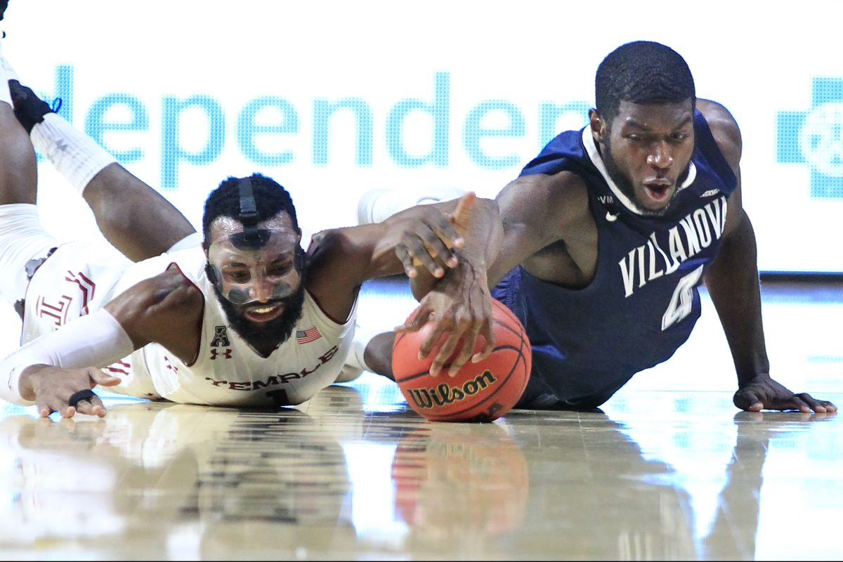 Josh Brown, left, of Temple and Eric Paschall of Villanova go after a loose ball in the 1st half at Liacouras Center at Temple University on Dec. 13, 2017.