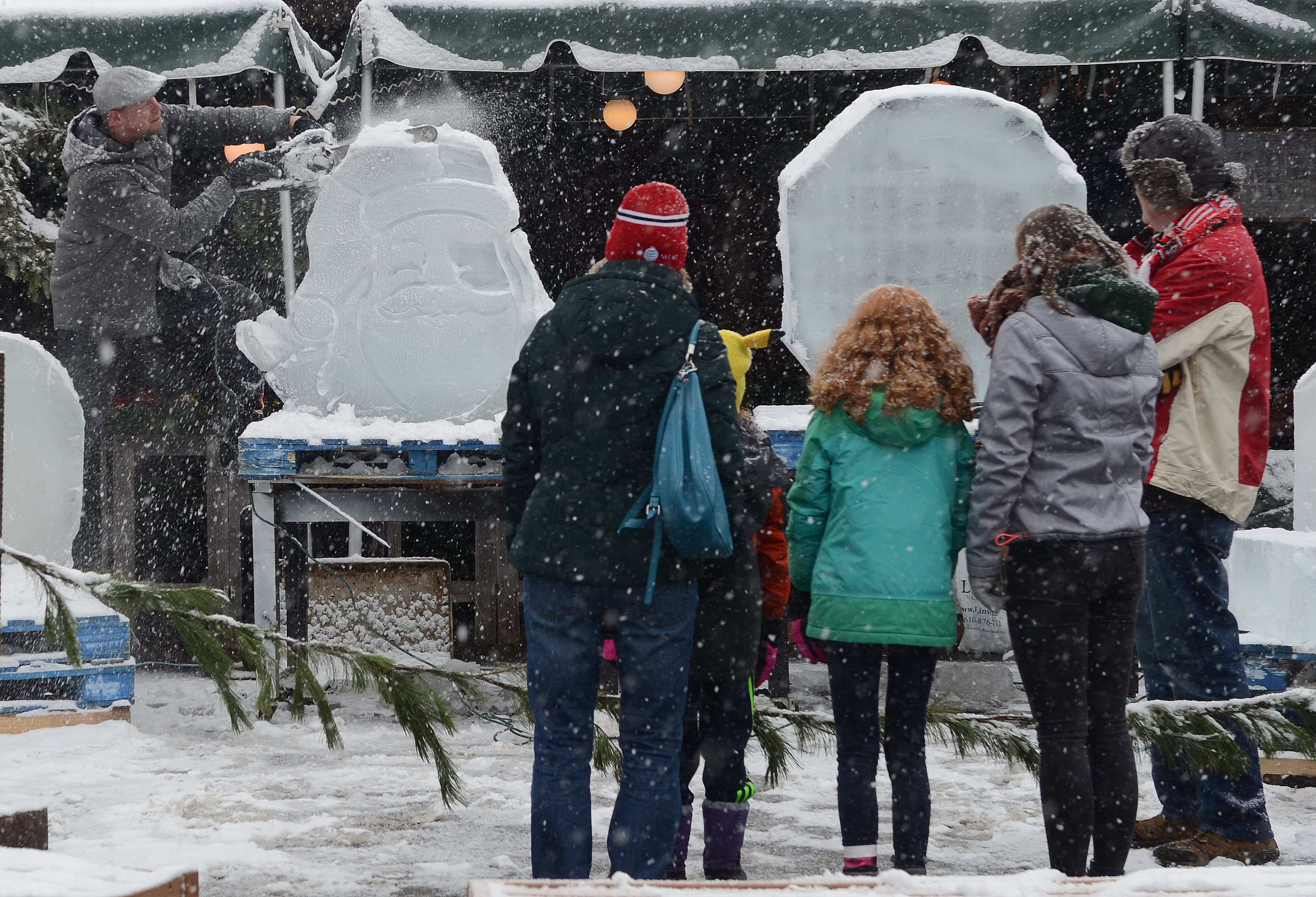 JOSE F. MORENO / Staff Photographer .Wynnewood residents, from left, Nuala Meyer, Lucy Meyer, Naeve Meyer, Lea Jung and Carl Meyer watch Don Lowing, perform his art of live ice carving, Saturday, December, 9, 2017, at the Linvilla Orchards, Media, PA. Lowing is one of only a handful of freehand ice sculptors in the area who still carve frozen art without the aid of computers. He does this on the side - his full-time job is at a local university.