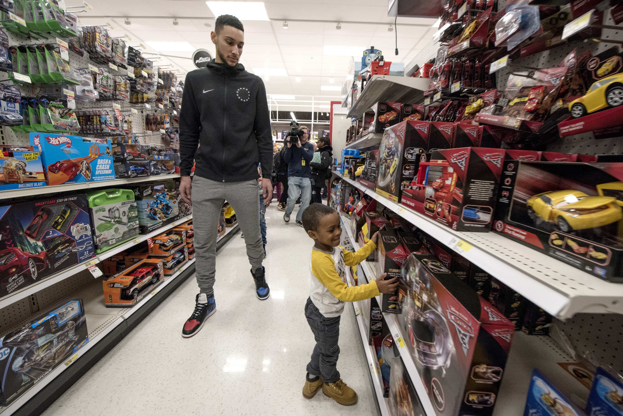 Sixers star rookie Ben Simmons watches Zaiden Johnson, 4, pick out a toy at the Target on Monument Road December 14, 2017. Simmons treated four families from the Unity in the Community organization of South Philadelphia to $1,000 each holiday shopping spree.