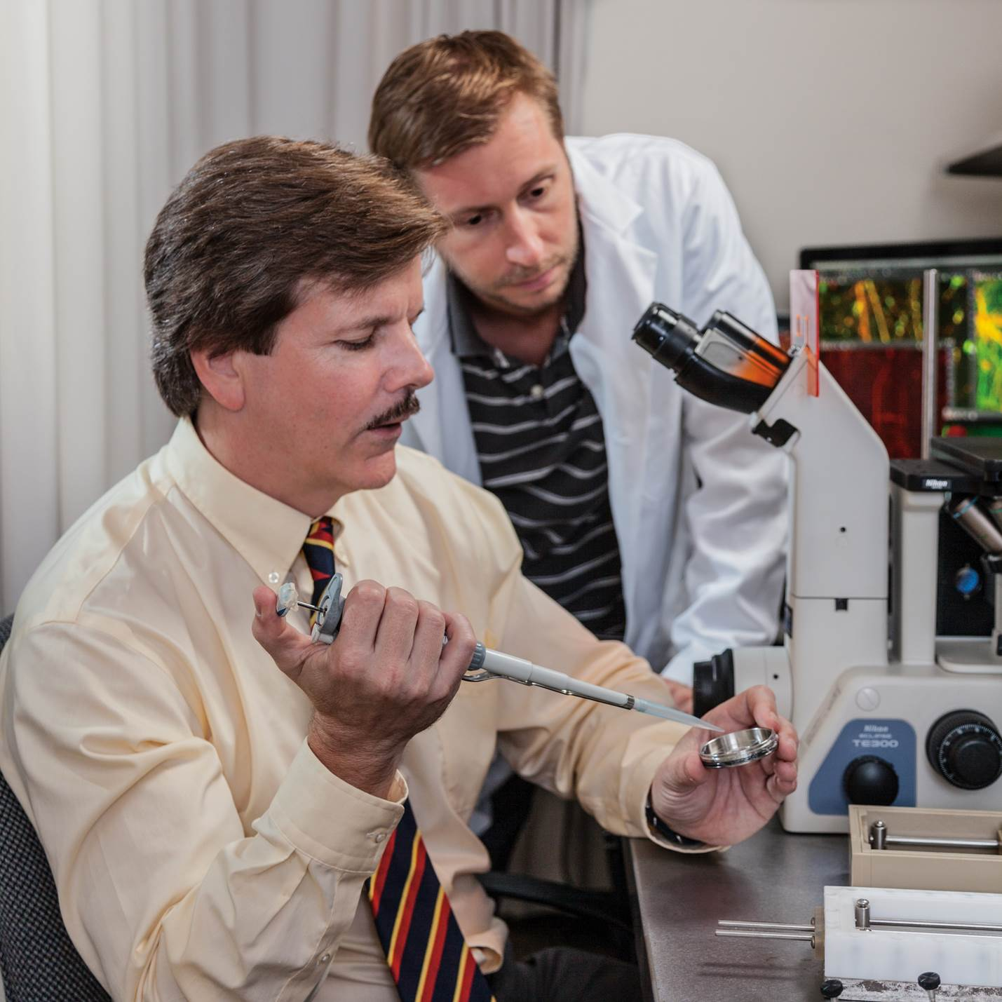 Douglas Smith, shown here with research specialist Andrew Jaye, investigates telltale changes of axonal injury in patients with mild concussion.