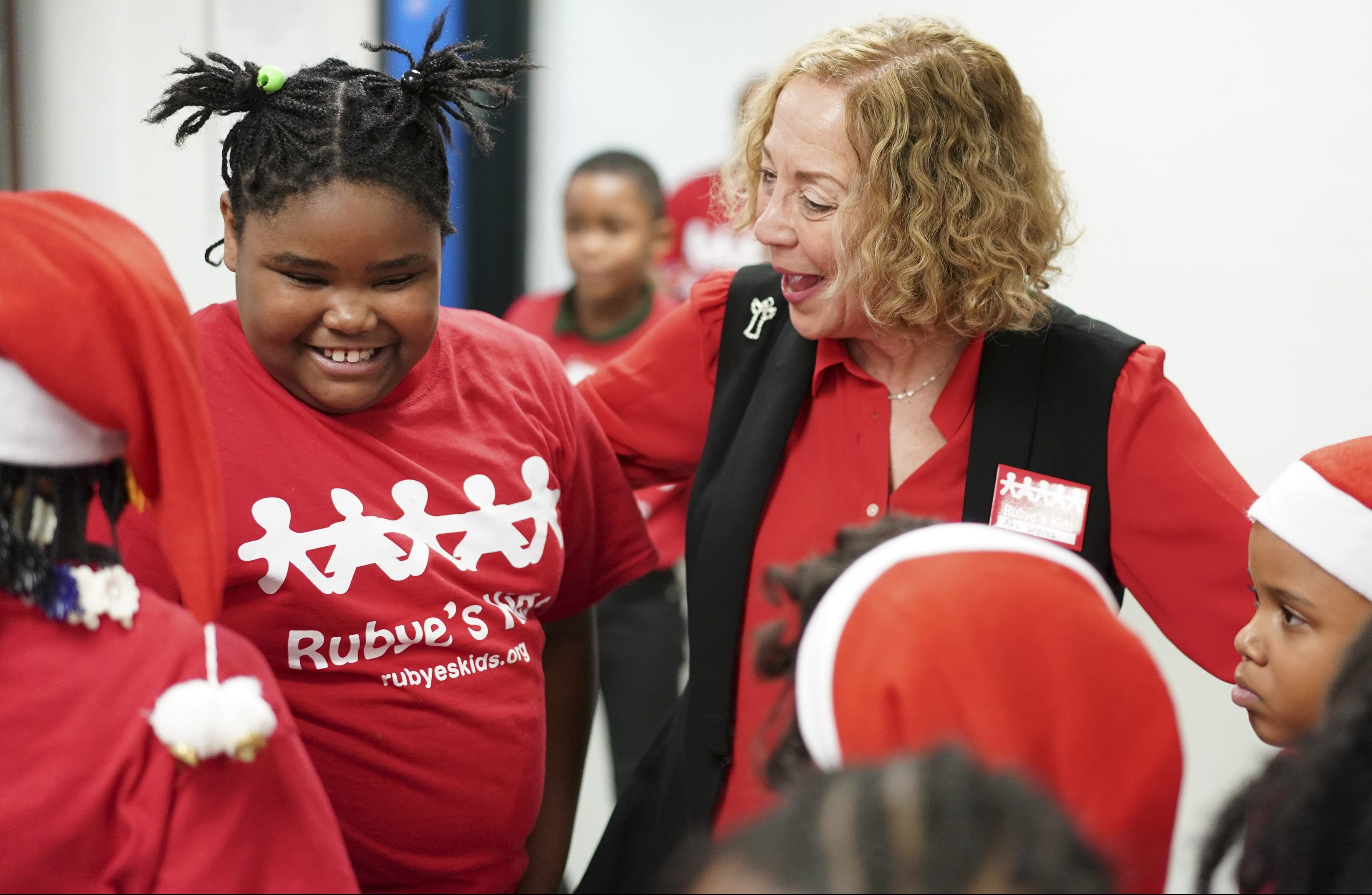 Rubye´s Kids founder Roz Weiss, right, talks with children during a Christmas Party hosted by Rubye´s Kids, Friday Dec. 15, 2017, at the Richard Wright Elementary School in North Philadelphia. Joseph Kaczmarek/ For the Inquirer