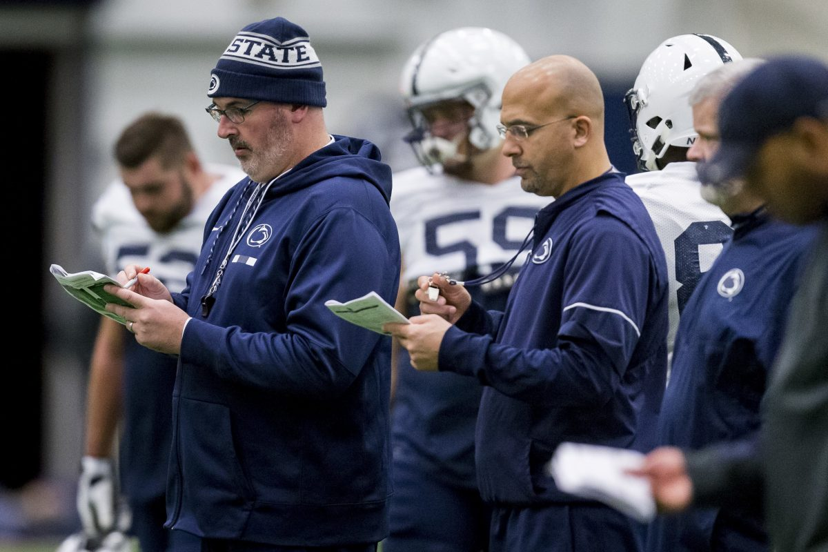 Penn State offensive coordinator Joe Moorhead, front left, and coach James Franklin check notes during NCAA college football practice Wednesday, Nov. 15, 2017, in State College, Pa.
