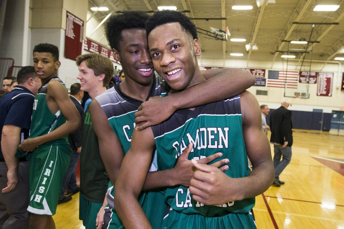 Uche Okafor (right) of Camden Catholic is hugged by Baba Ajike after Okafor's basket proved to be the difference in 50-48 victory over Eastern in their season opener in boys' basketball.