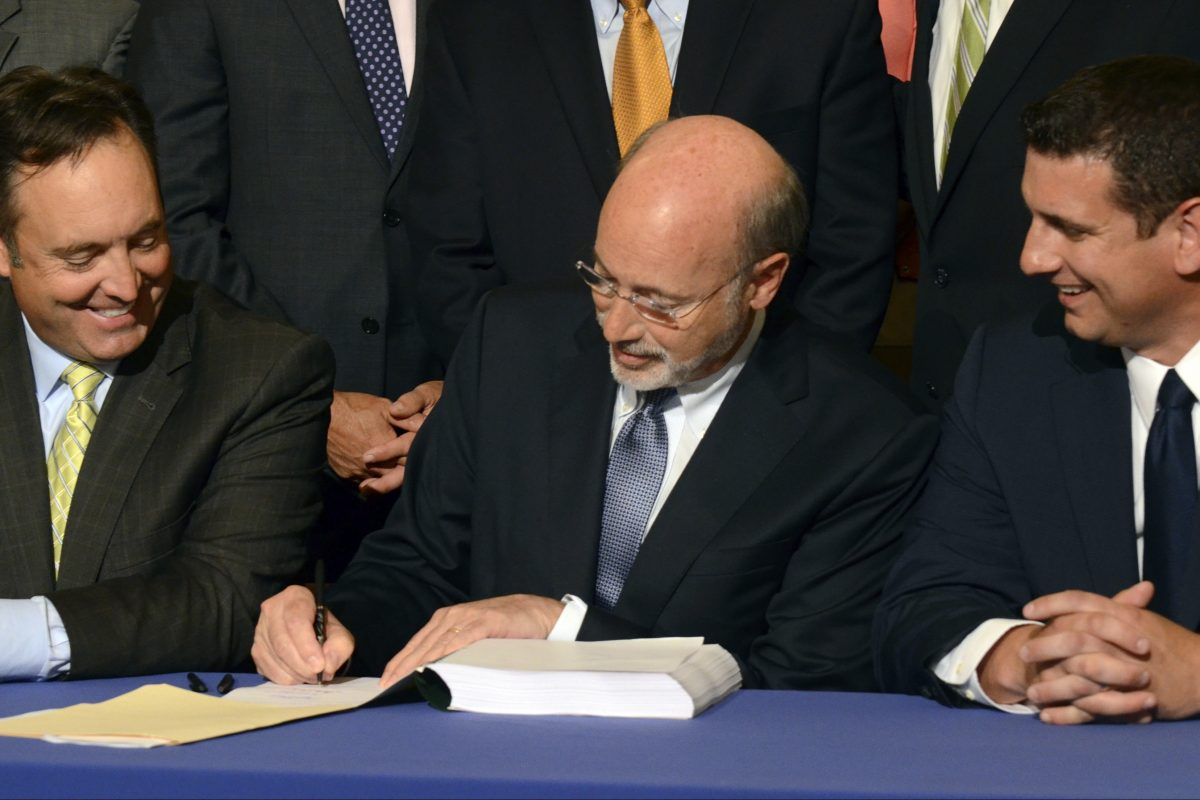 Democratic Gov. Tom Wolf signs legislation designed to reduce long-term public pension costs during a signing ceremony in the Pennsylvania Capitol on Monday, June 12, 2017 in Harrisburg, Pa. Looking on are Senate Majority Leader Jake Corman, R-Centre, right, and House Majority Leader Dave Reed, R-Indiana. (AP Photo/Marc Levy)