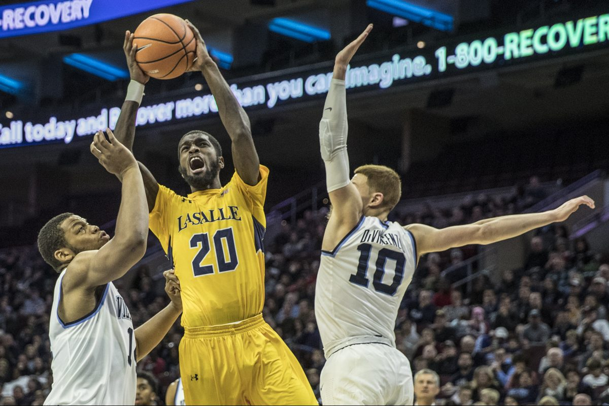 La salle's 320, B.J. Johnson, center, tries to go in between the defense of Villanova's #14, Omari Spellman, left, and #10, Donte DiVincenzo, right, in the second half of their game on Sunday December 10, 2017. Mens college basketball La Salle at Villanova at Wells Fargo Center on Sunday December 10, 2017.