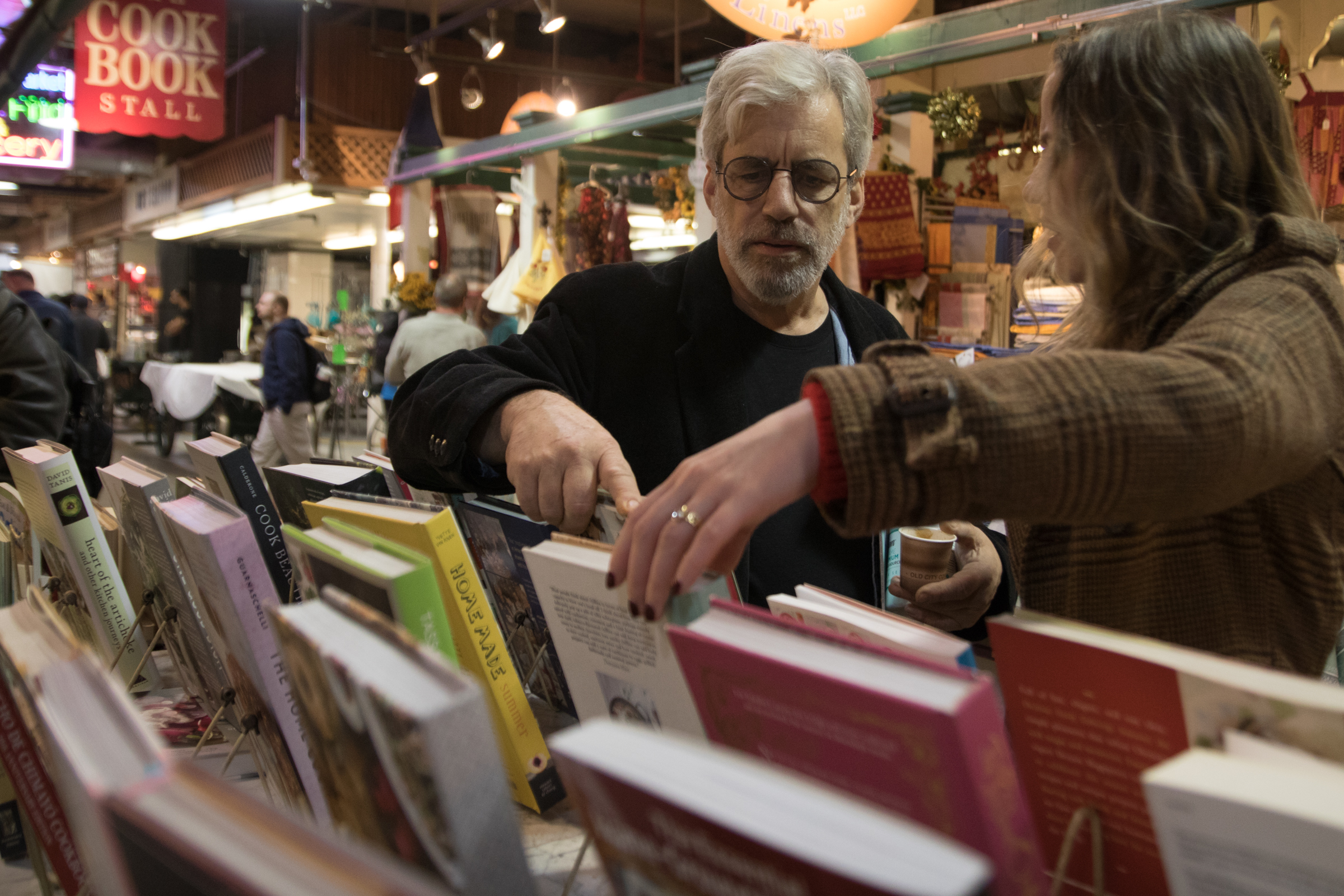David Tanis looks at cookbooks at the Cook Book Stall at Reading Terminal Market with Danielle Mulholland, who works for CookNSolo Restaurants.