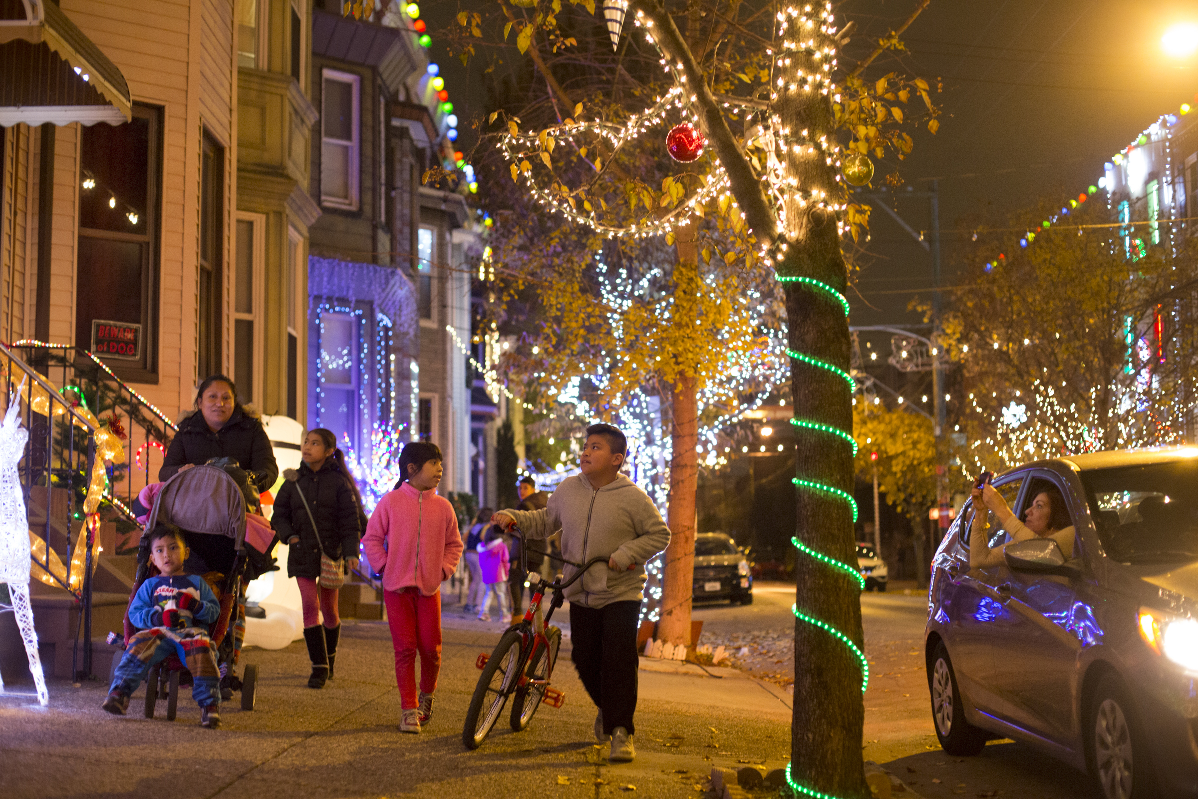 """Magdalena Vazquez walks with her children, Alan Ruiz, 3, Ashley Ruiz, 11, Carolina Ruiz, 10, and Alexis Ruiz, 10, through the 1600 block of South 13th street where lights are being put up for the """"Miracle on South 13th Street"""" Friday, November 25, 2016."""