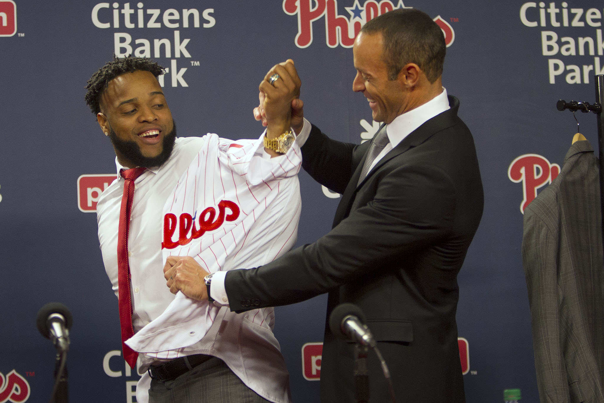 Philadelphia Phillies manager Gabe Kapler, helps newly signed first baseman Carlos Santana with his jersey as he was introduced to the media during a press conference, Wednesday, December 20, 2017.