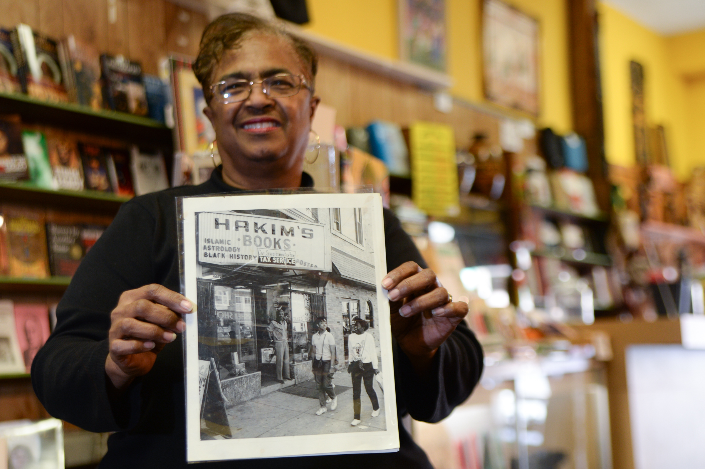 Yvonne Blake holds a photo of her father Dawud Hakim in front of the store in the 1970s.