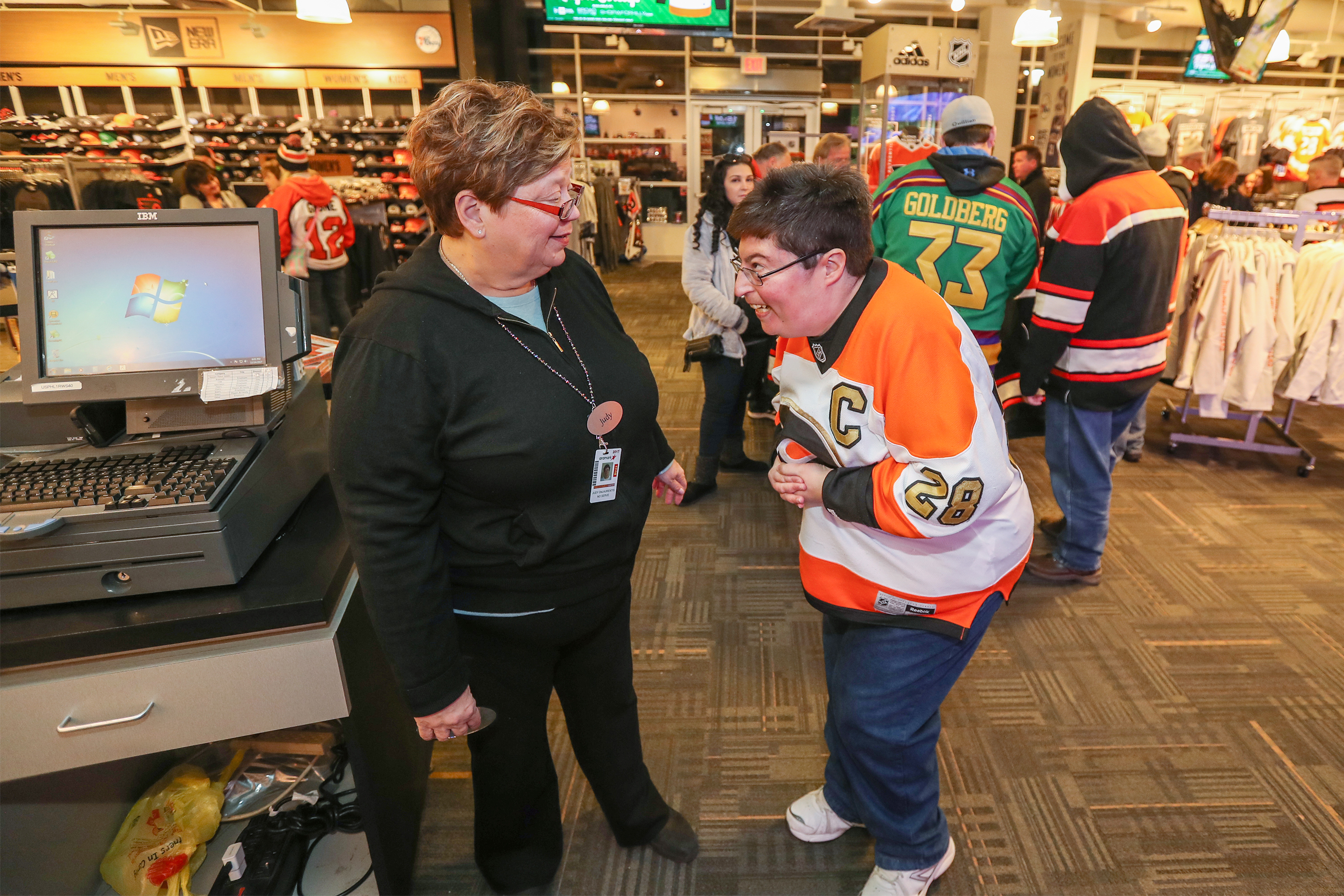 Josh Silverman, right, gets very excited talking about the upcoming game against the Buffalo Sabres while talking to Judy DeLaurentiis, left, who works in the New Era Team Store in the Wells Fargo Center. MICHAEL BRYANT/ Staff Photographer