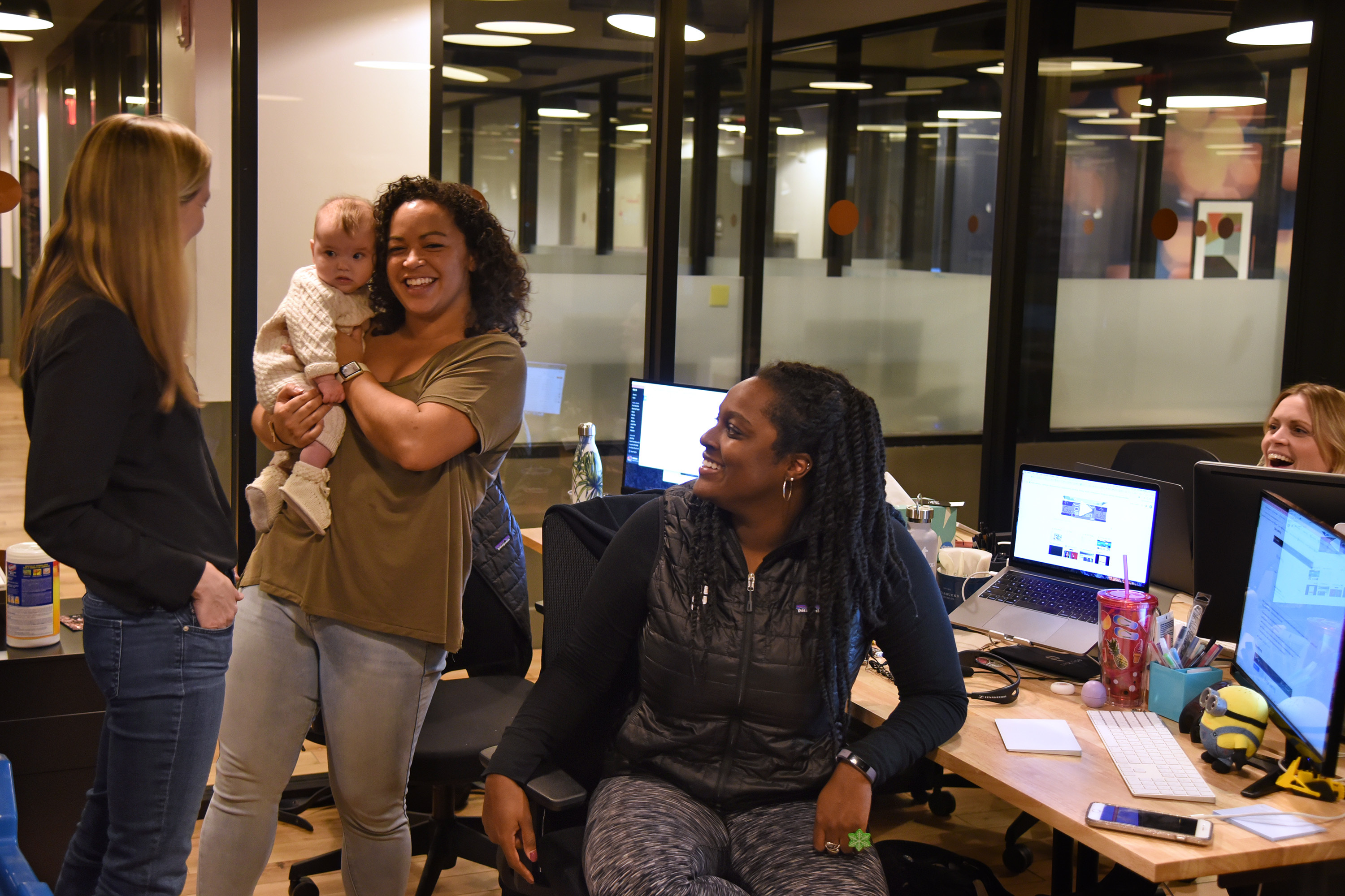 Tech startup founder and mom Emily Foote (left) with daughter Hazel Marie Williams, 4 months, held by Ashley Karpeh during work at Practice XYZ, Inc. December 21, 2017. Seated is K'Shelle Waller. At far right , partially hidden is Alyson Emmett.