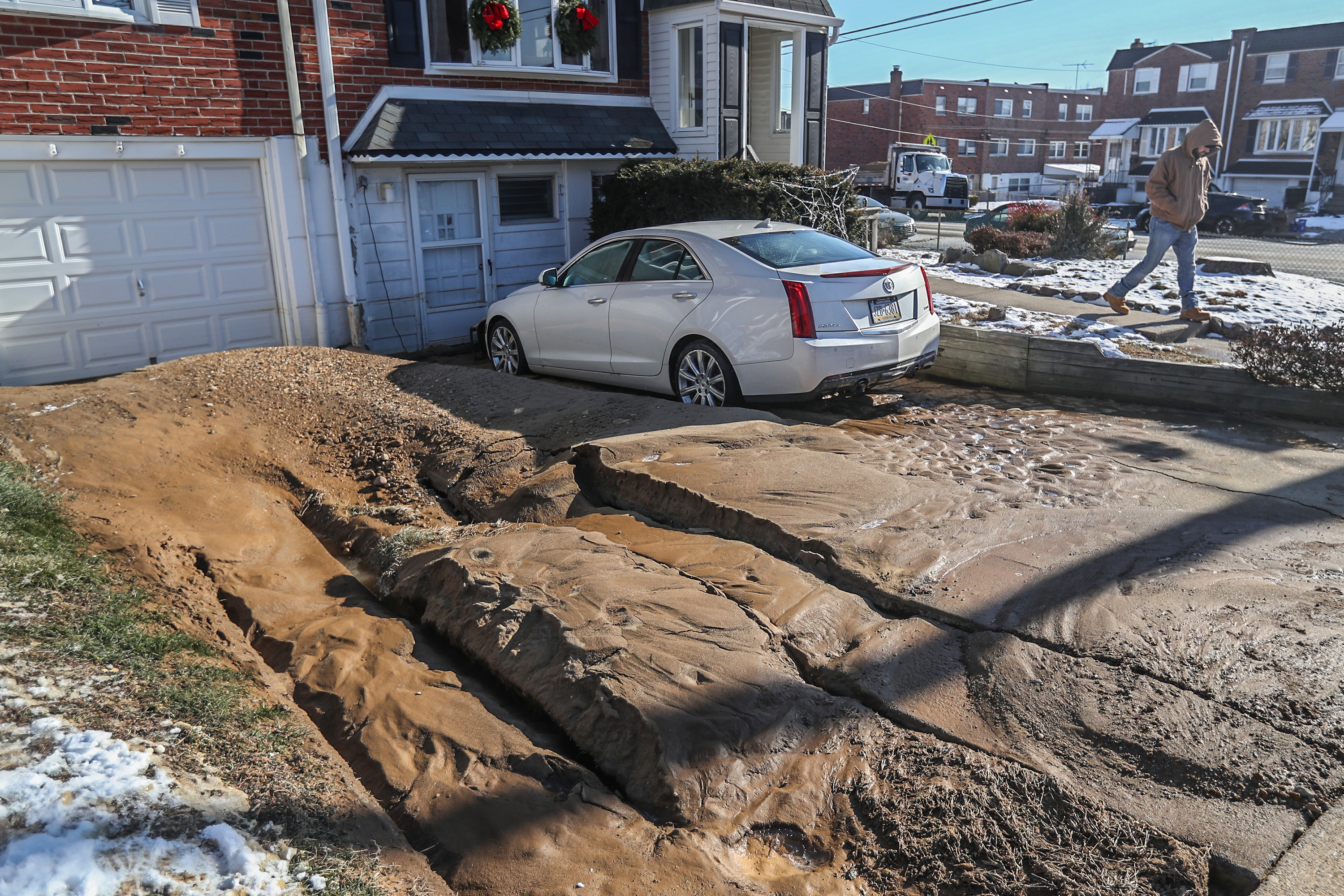 Several feet of mud ended up in the dual driveways of homes on Minden Road after an 8 inch water main burst early on Tuesday morning. The car that is parked was covered with water over the front hood. Philadelphia Water Department was working on repairs. MICHAEL BRYANT/ Staff Photographer