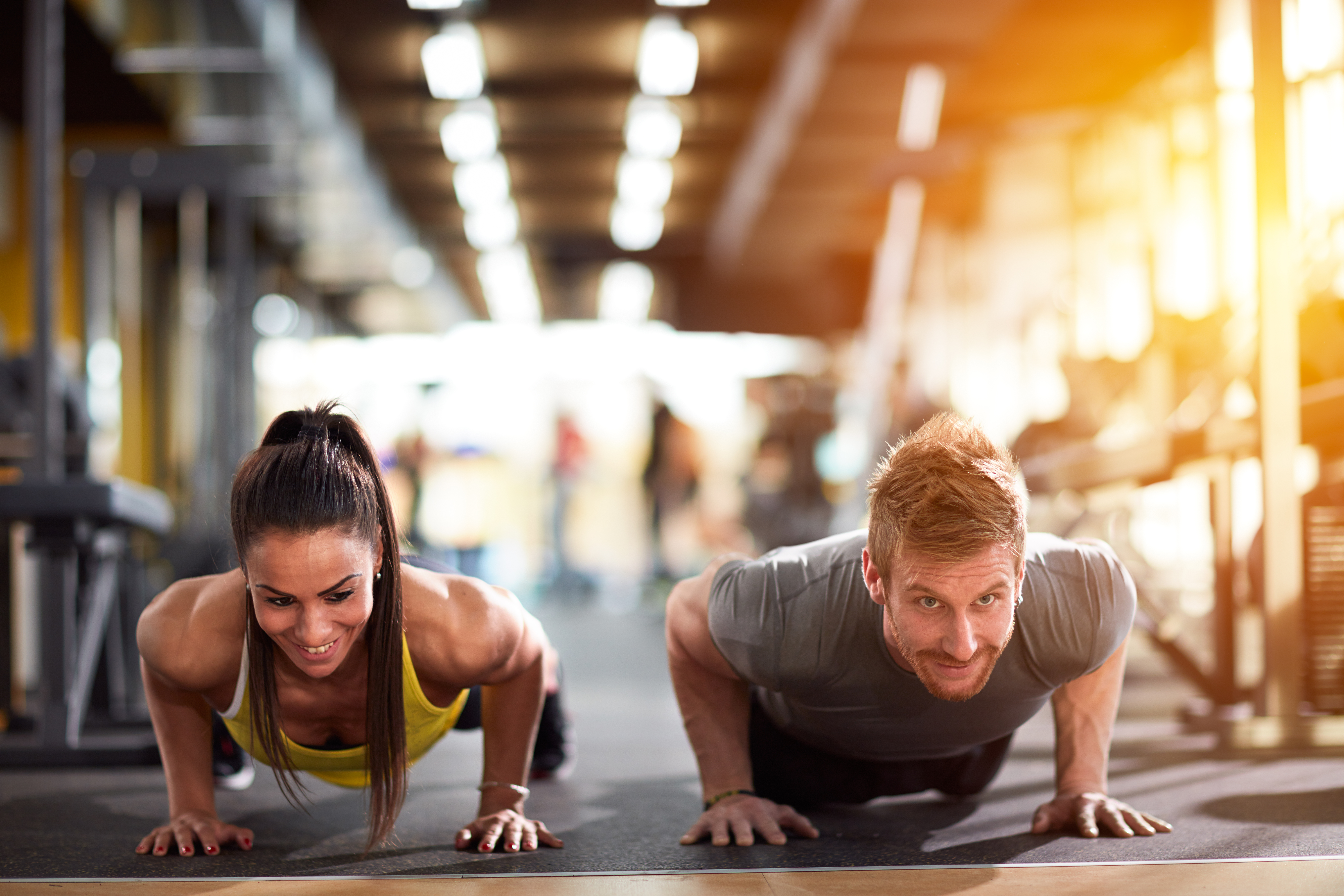 Couple doing pushups at training in gym