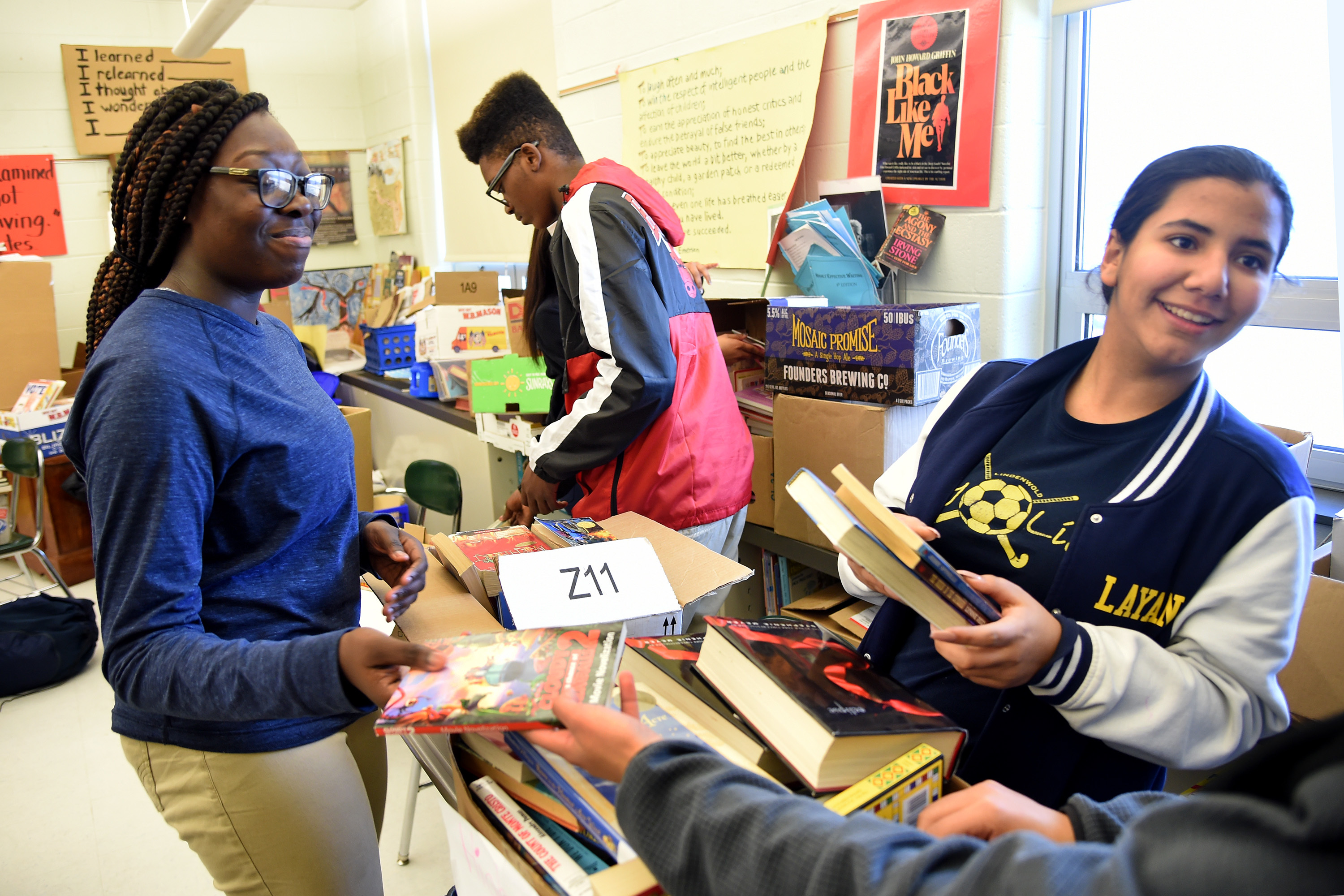 Students of Lindenwold High School English teacher Larry Abrams (not shown), Olivia Meizan (from left) Jayden Brown, and Layan Muhamed sort books to give away January 3, 2018. Abrams has started a book collection and donation charity to help his low-income students, many of whom had poor literacy skills in his 9th grade English class. He collects from all over the region and distributes at school functions. He´s hoping to expand the concept to other poor districts in the region. TOM GRALISH / Staff Photographer