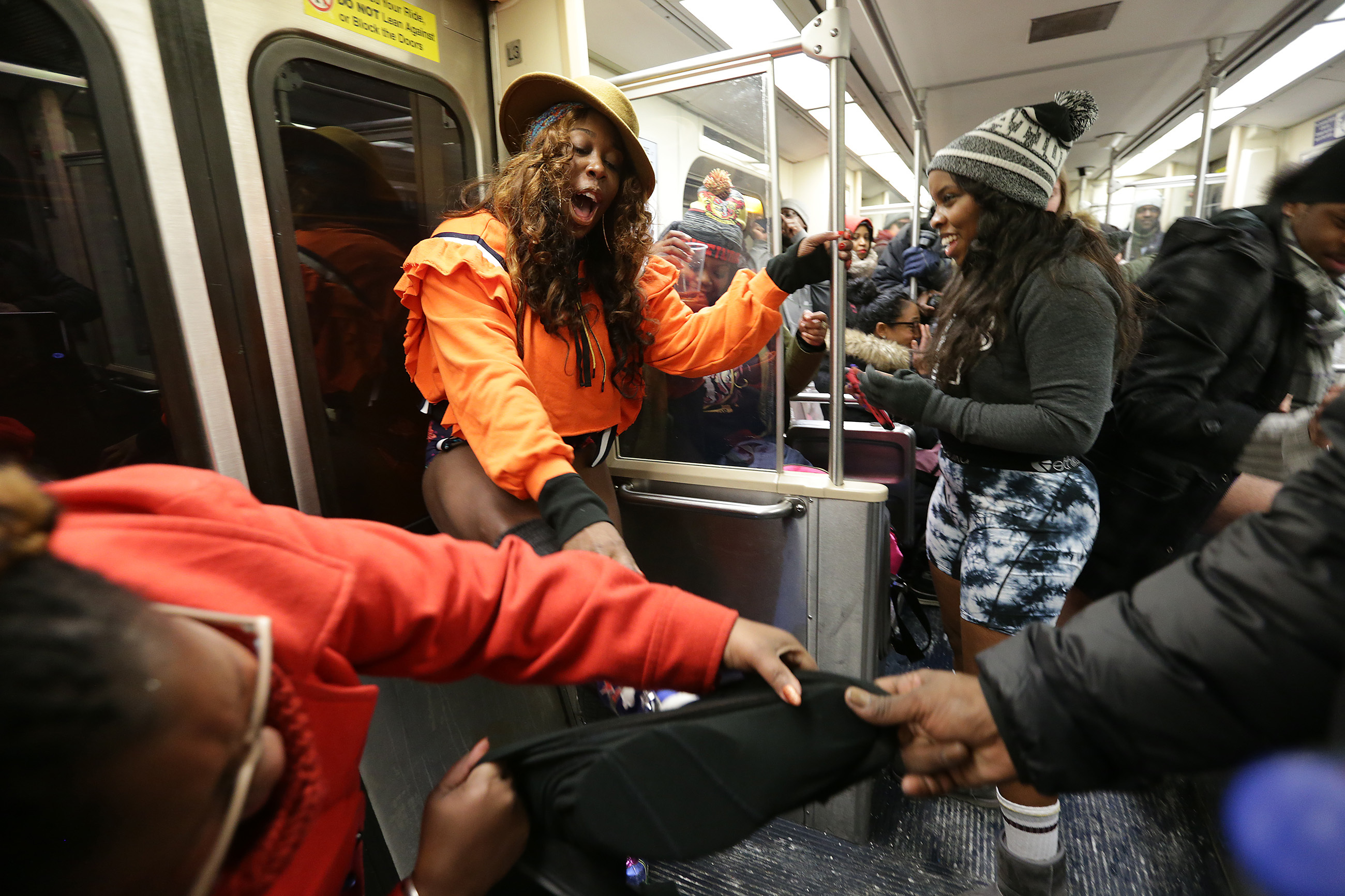 India White, center, gets help undressing during the No Pants Subway Ride in Philadelphia, PA on January 7, 2018.