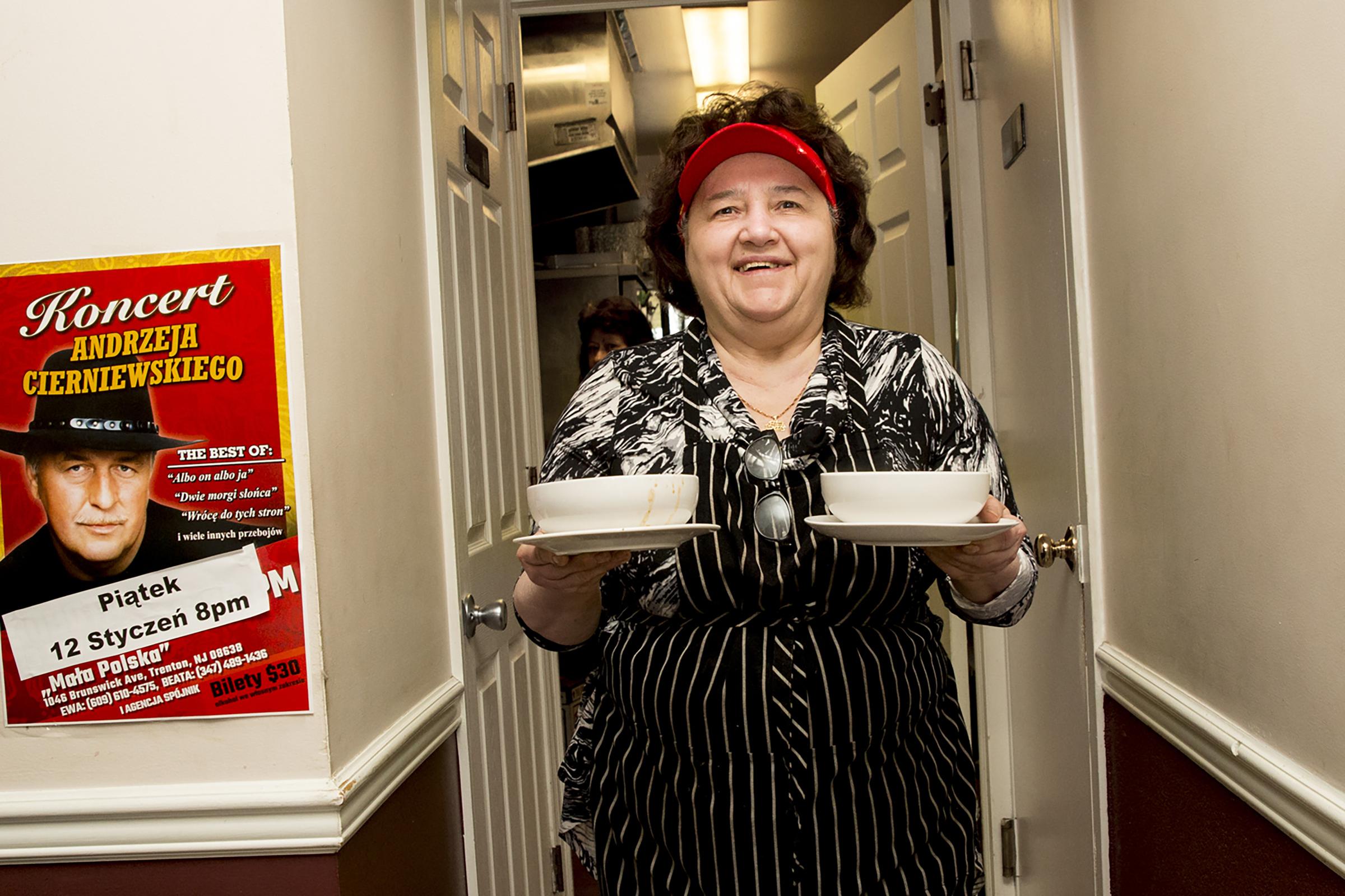 Chef Ela Balka carries bowls of soup.