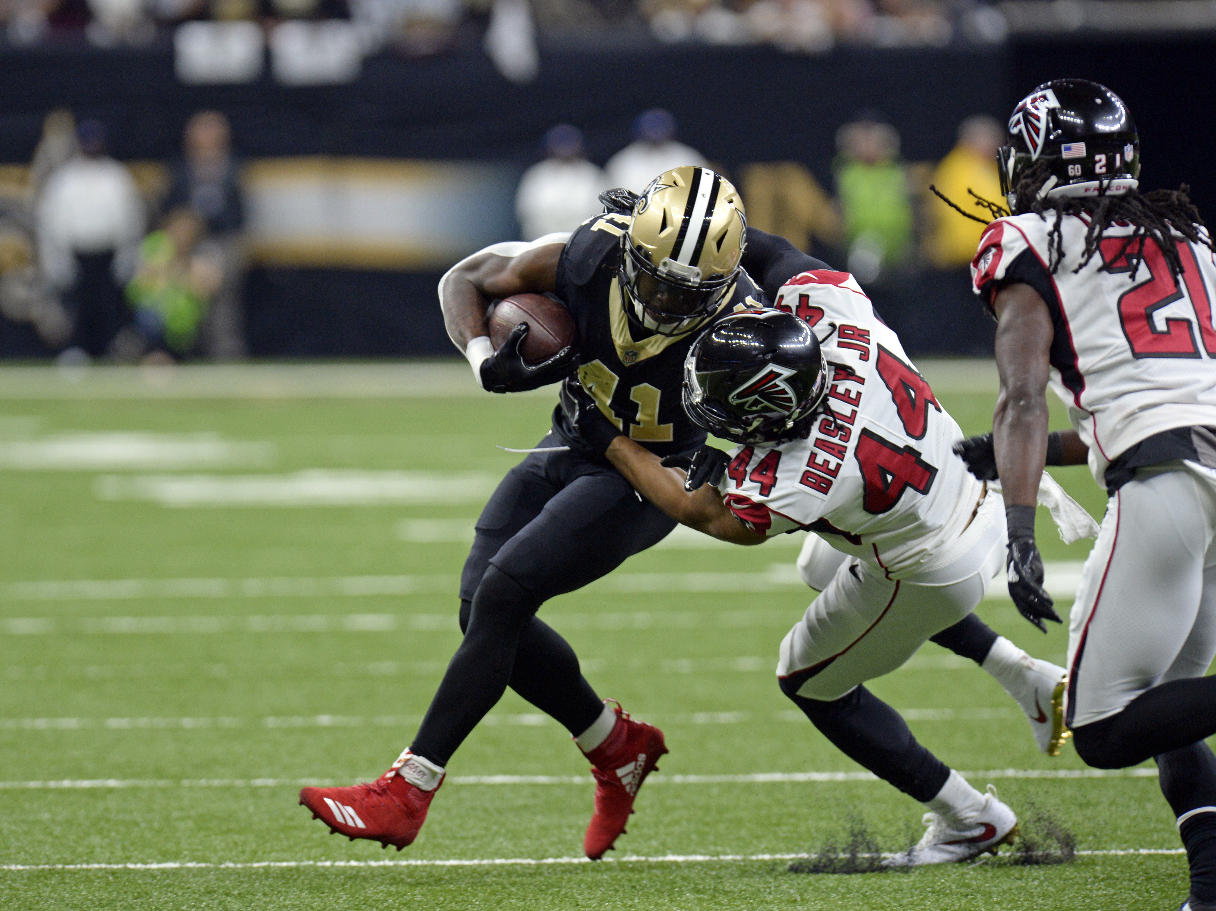 Falcons outside linebacker Vic Beasley (44) tries to tackle Saints running back Alvin Kamara (left) on December 24, 2017.
