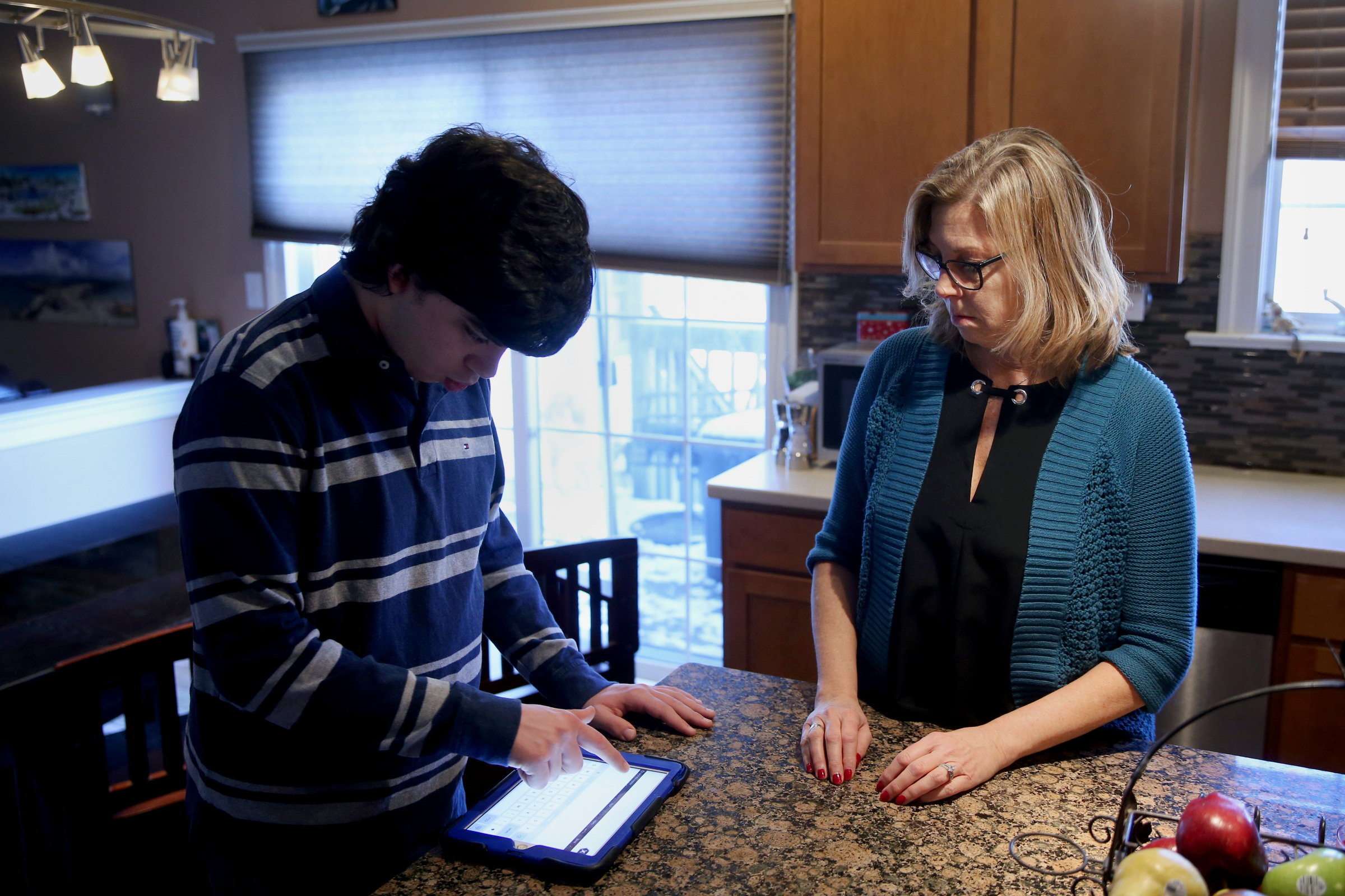 Stefan Velocci, 21, left, uses an iPad with the Proloquo2Go alternative communication app with his mom, Karen, at their home