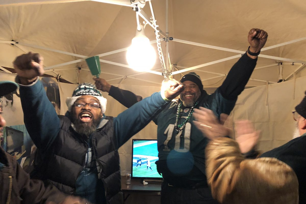 """Thomas """"Fattz"""" Walker and Derrick """"Big Derrick"""" Simmons celebrate in their tent outside the Linc after the Eagles victory."""