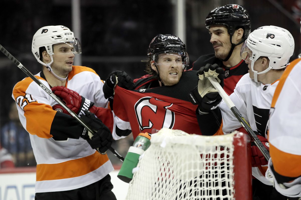 Flyers' Scott Laughton (left) and defenseman Travis Sanheim argue with Devils' Blake Coleman (center left) and Brian Boyle during the second period.