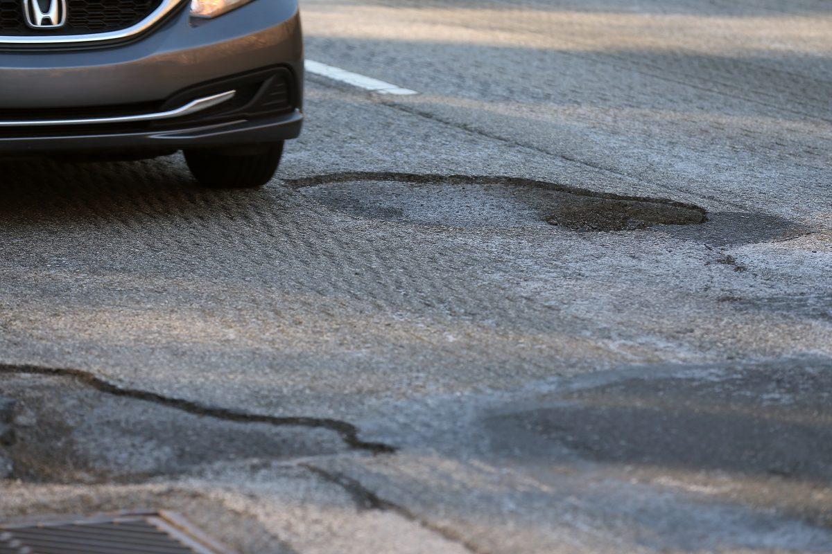 A car avoids a pothole on Lincoln Drive near Gypsy Lane in Philadelphia on January 14, 2018.