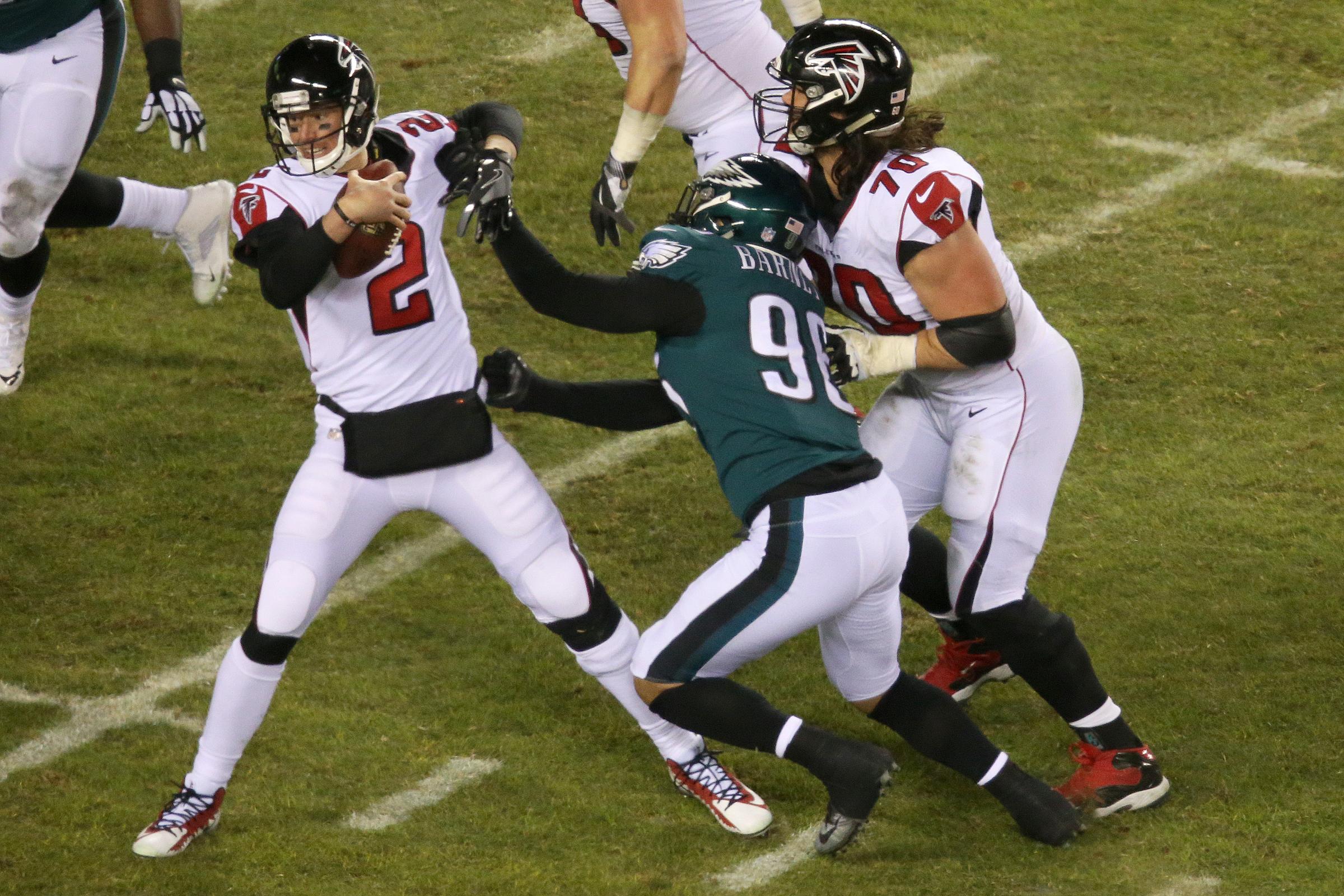 Falcons quarterback Matt Ryan (2) fending off a sack attempt by Eagles defensive end Derek Barnett (96) during the first half.