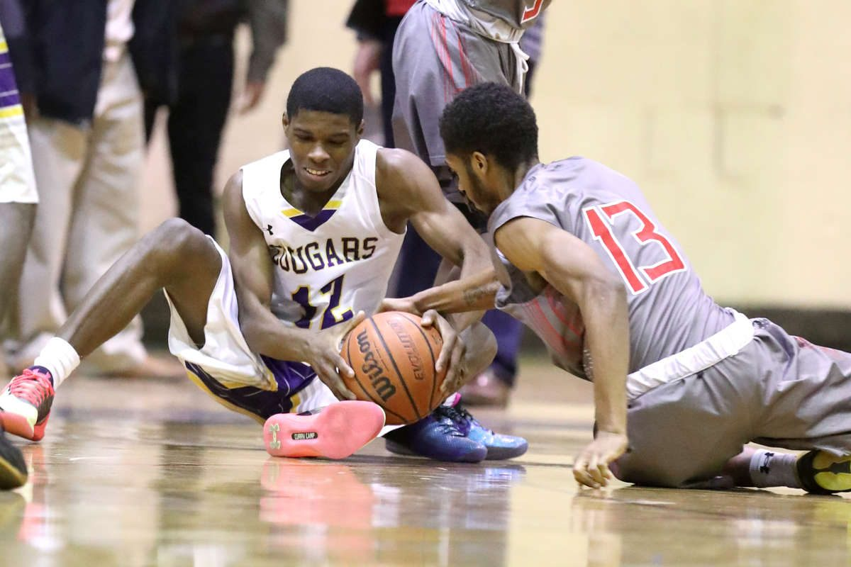 Hyseir Miller, left, of Martin Luther King and Amear Johnson of Imhotep Charter scramble for a loose ball in the 4th quarter on Jan 18, 2018.