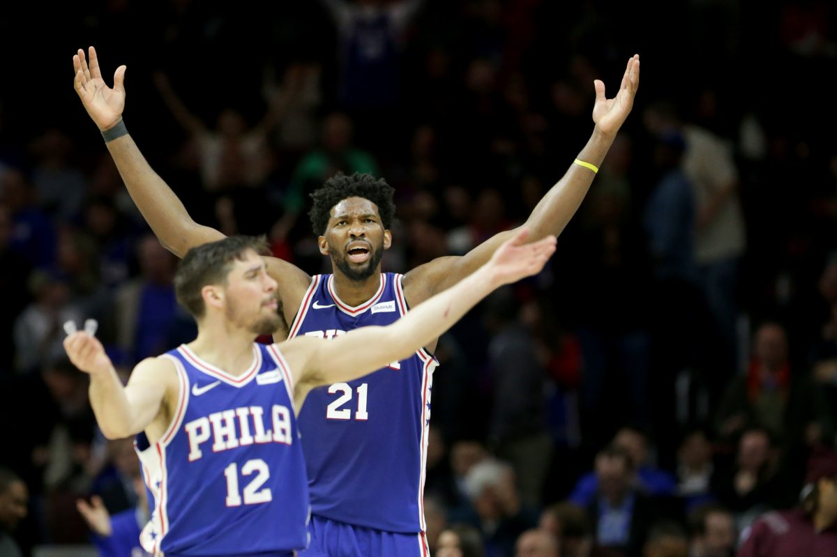 Sixers T.J. McConnell, left, and Joel Embiid, right, play to the crowd during the 4th quarter against the Toronto Raptors on January 15, 2018.