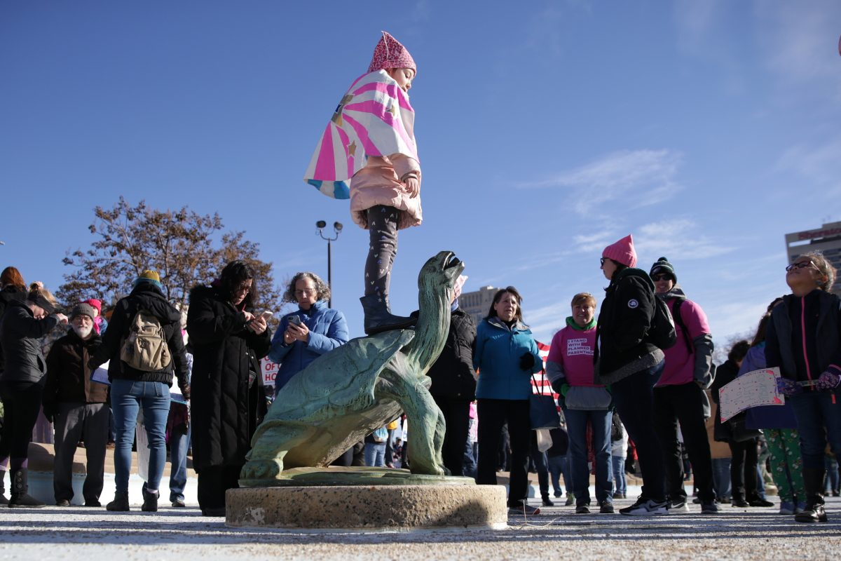 Vivien Kanienberg, 6, of Willmington, Del., stands on the turtle sculpture in Logan Fountain during the Women's March on Philadelphia, on Jan. 20, 2018.