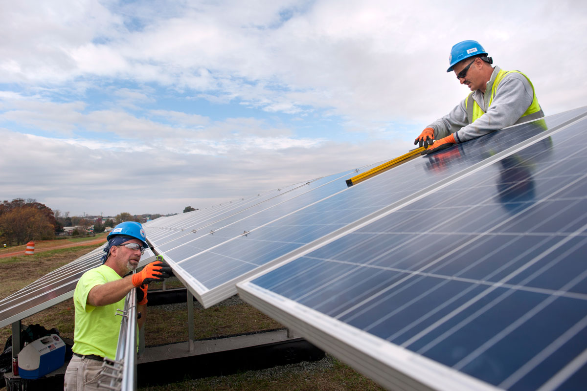 Workers install solar panels in 2015 on a Lumberton, N.J., landfill. Analysts say that such utility-scale projects are most likely to be affected by new U.S. tariffs on solar panels.