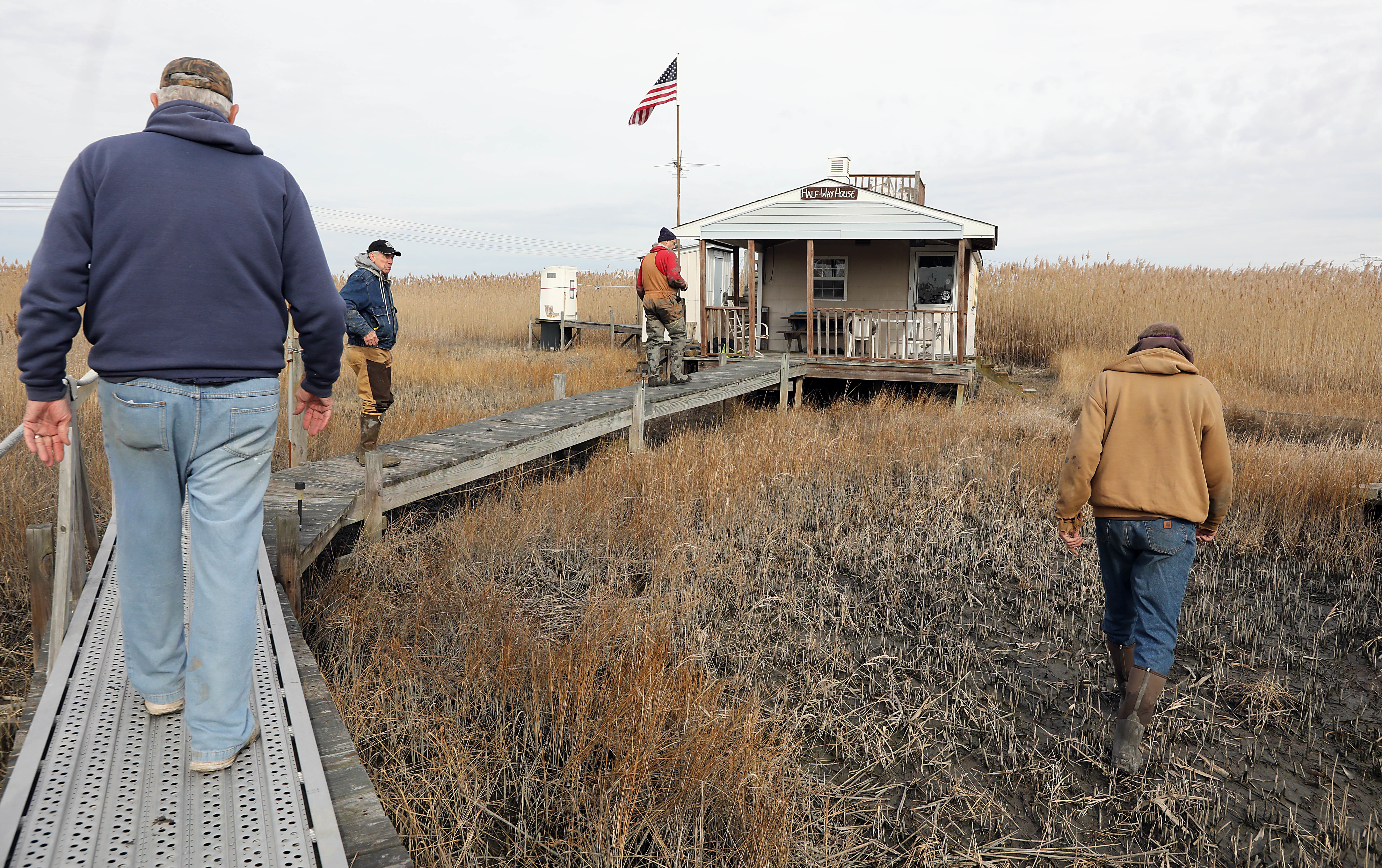 CABINS23-D 01-22-2018.(AKIRA SUWA / For The Inquirer).DEP is removing cabins along the creek on protected waterfront in Salem County,NJ.L to R. Chuck Liber, 72, his brother, Bob Liber,79 Bob´s son Matt Liber51 and John Clendining,60 who has a cabin in his property are walking toward to a Liber family´s Cabin in their property near Hope Creek & Delaware River.