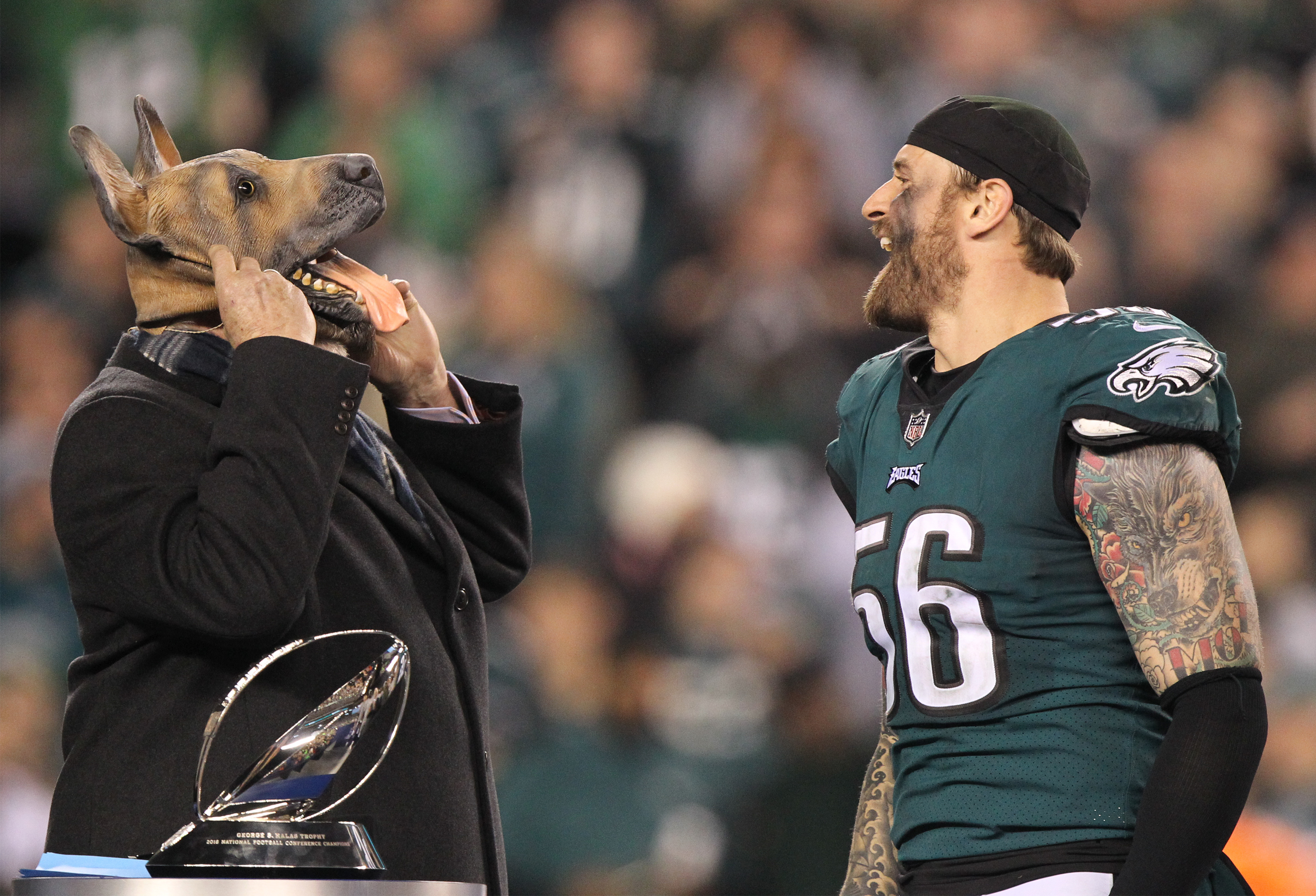 Eagle defensive end Chris Long, right, erupts in laughter as Terry Bradshaw dons a dog mask on the podium during the award ceremony for the NFC championship on Sunday night.