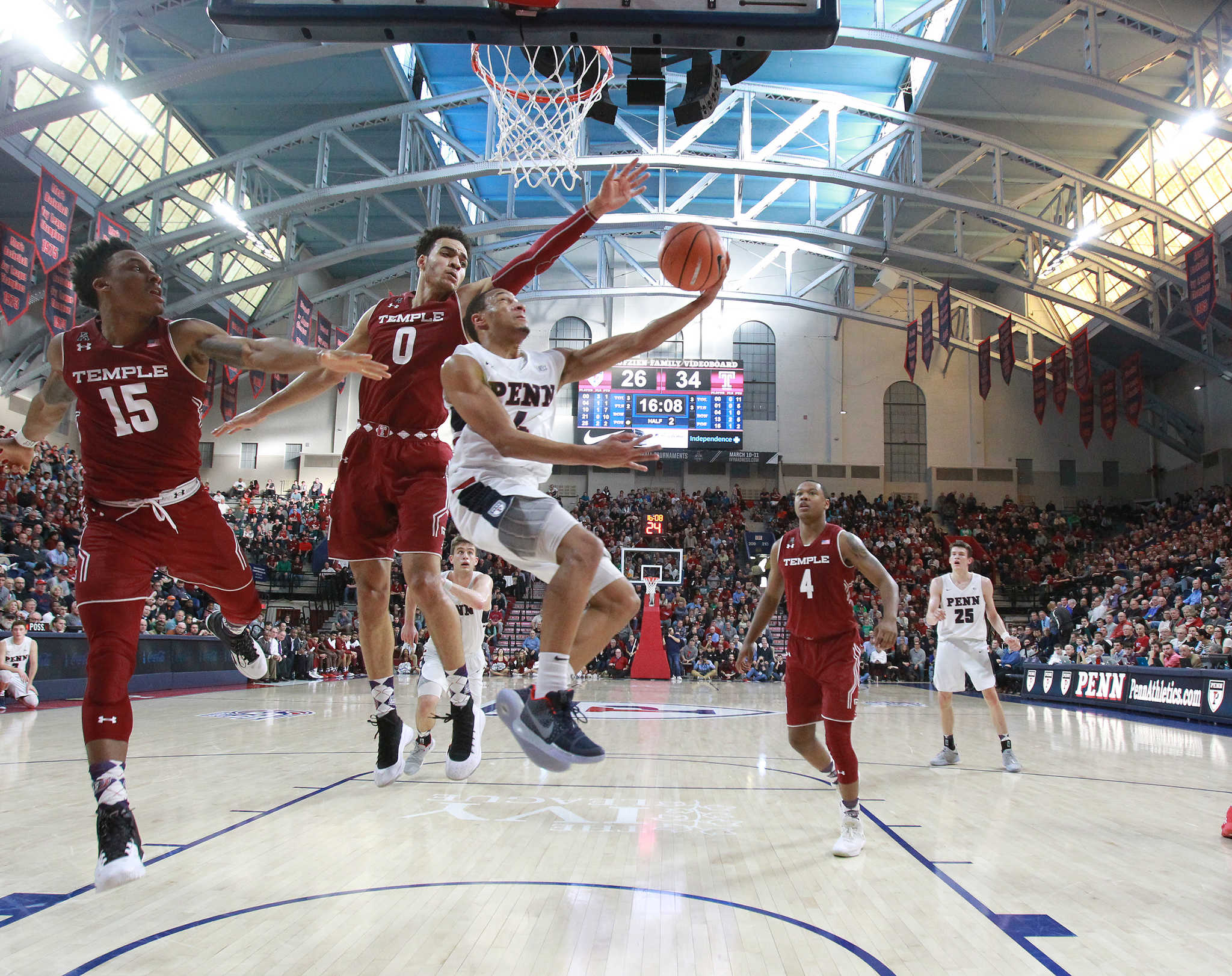 Darnell Foreman, center, of Penn splits Nate Pierre-Louis, left, and Obi Enechionyia, 2nd from left, of Temple during the 2nd half at the Palestra on Jan 20, 2018.