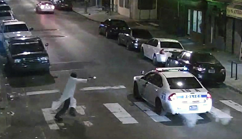 In this frame from a Thursday, Jan. 7, 2016 video provided by the Philadelphia Police Department, Edward Archer runs with a gun toward a police car driven by Officer Jesse Hartnett in Philadelphia. Archer, using a gun stolen from police, said he was acting in the name of Islam when he ambushed Hartnett sitting in his marked cruiser at an intersection, firing shots at point-blank range, authorities said. (Philadelphia Police Department via AP) YEAREND2016