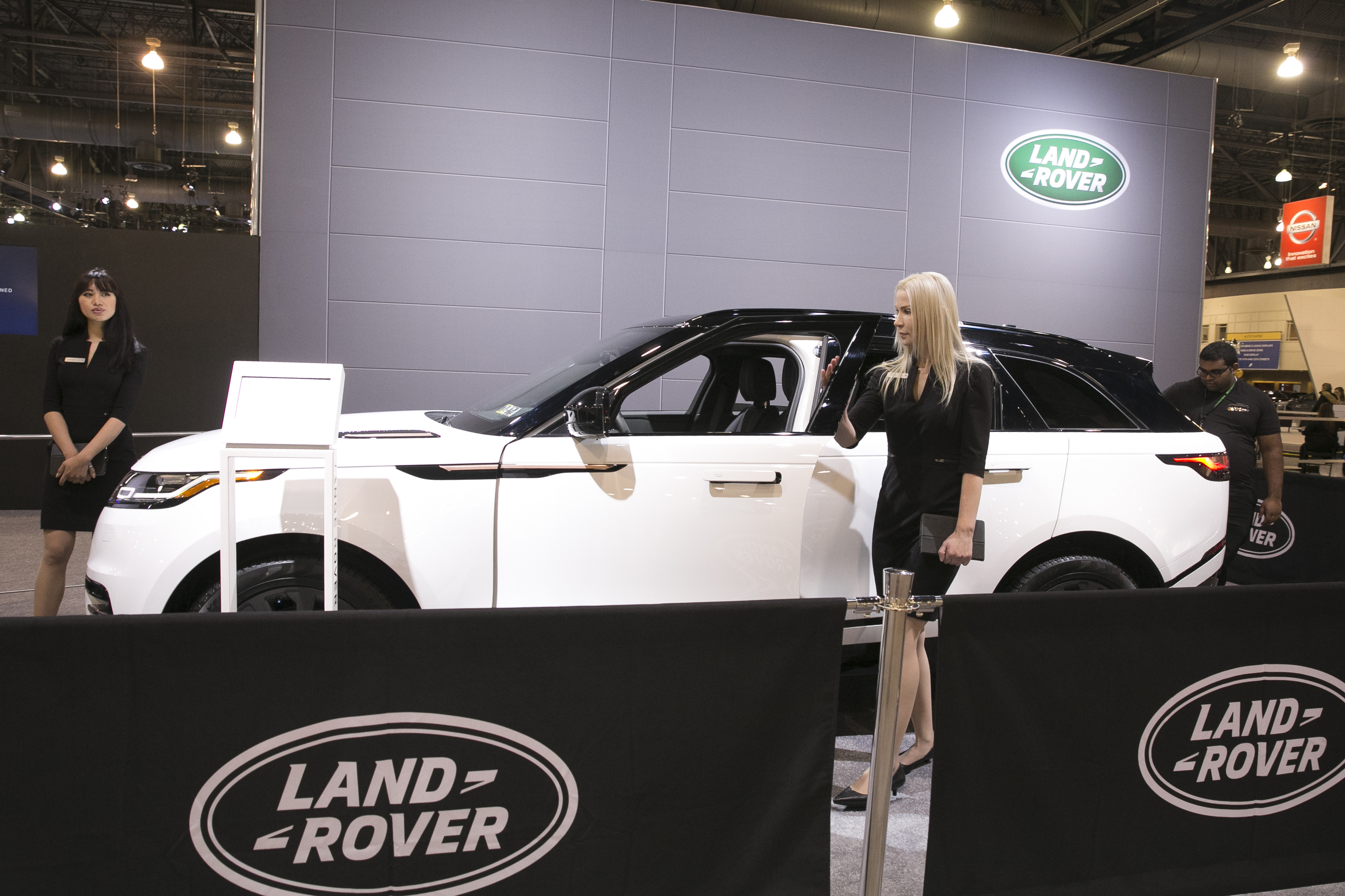 Julienne De Leon, left, and Mary Boike, center, stand near a Range Rover Velar, during the Manufacturers´ preview of the Philadelphia Auto Show, at the Philadelphia Convention Center, Friday, Jan. 26, 2018. JESSICA GRIFFIN / Staff Photographer