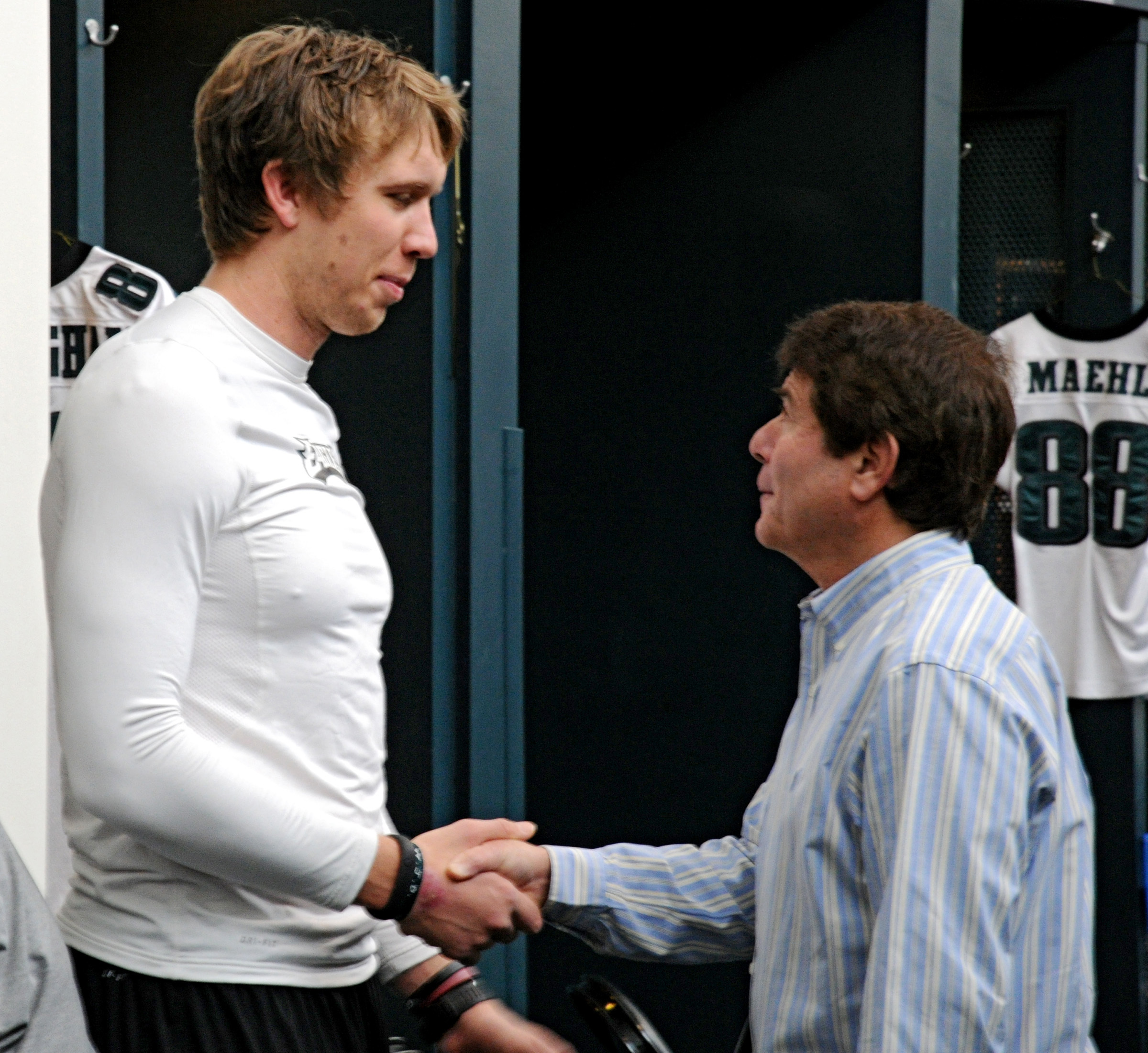 Merrill Reese greets Eagles quarterback Nick Foles (left) in the locker room in January 2014.