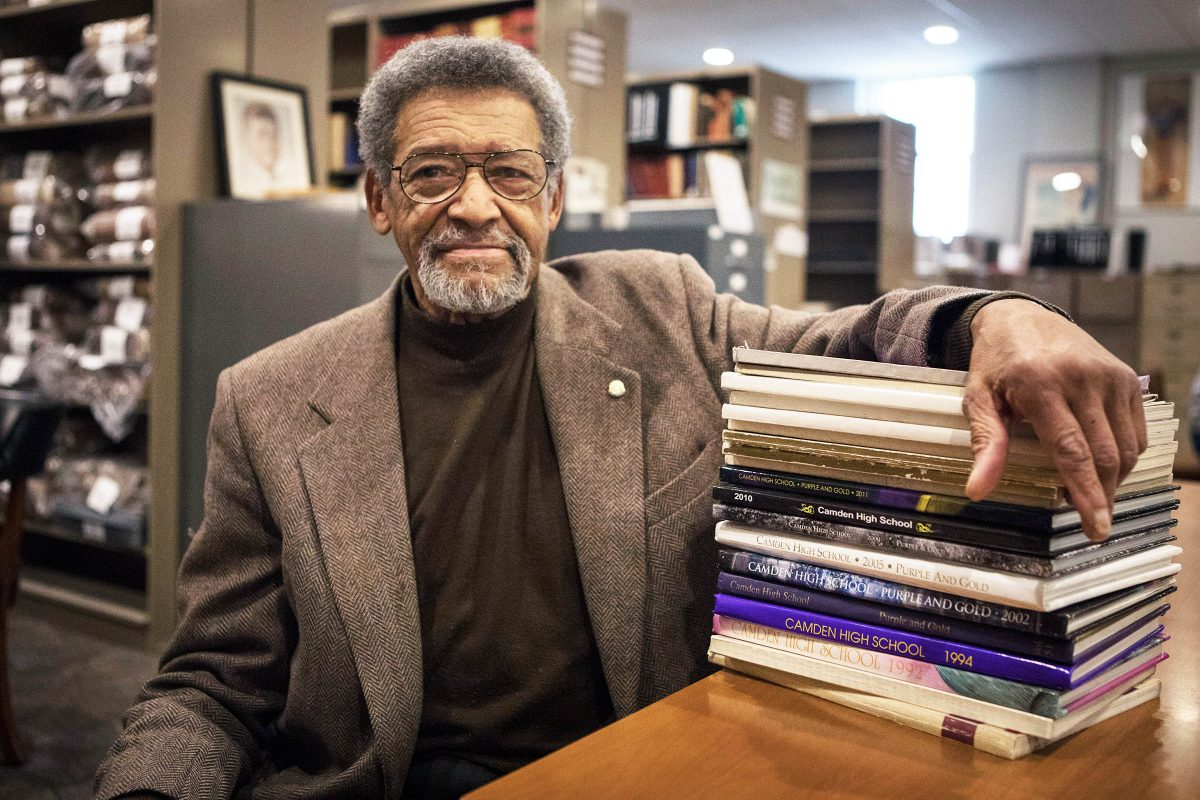 "Kelly Francis, longtime Camden, NJ resident and NAACP leader, sits with a stack of Camden High School yearbooks at the Camden County Historical Society. He graduated from Camden High in 1952 and does not want to see ""The Castle on the Hill"" razed."