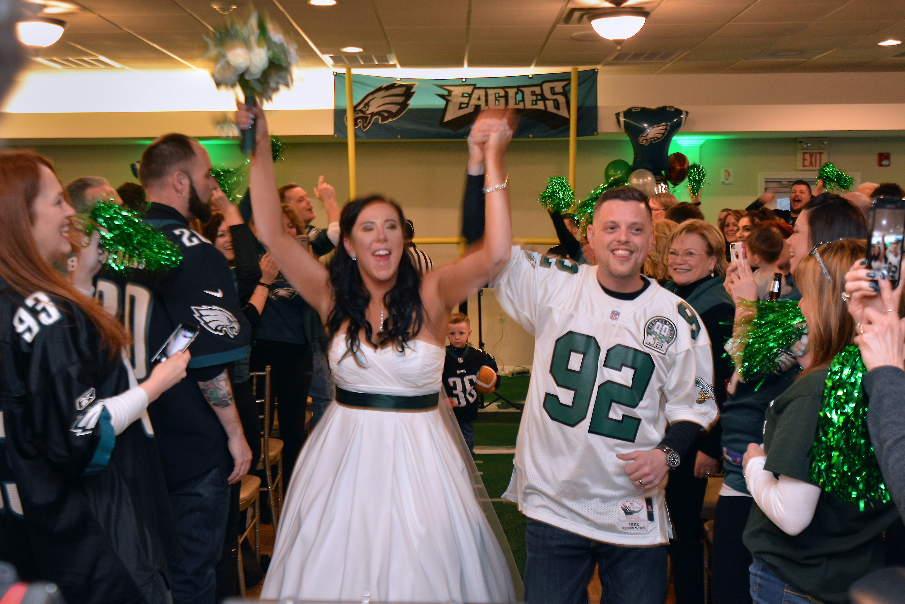 Newlyweds Sabrina Seneca and Christian Regalbuto rejoice as they walk up the aisle after their vows in their Eagles themed wedding at the Bensalem Country Club on Sunday 4,2018. Mark C Psoras/For the Inquirer