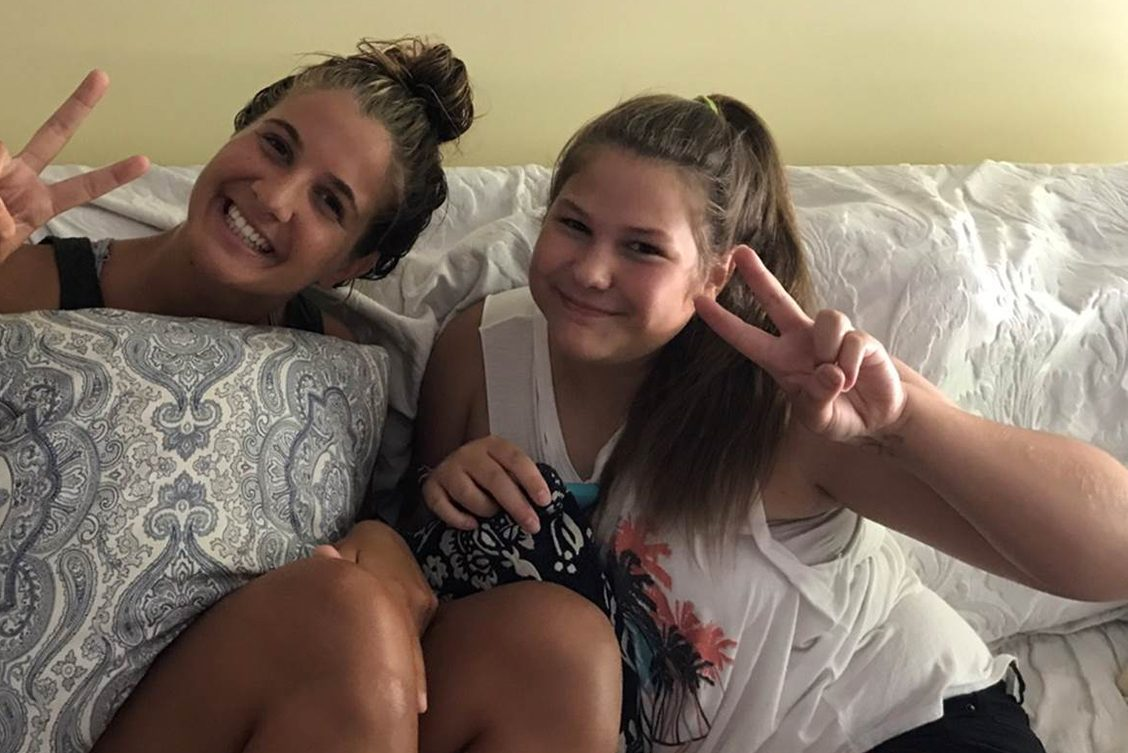 Almost five years free of leukemia, Tori Lee (right), 14, flashes a peace sign as she laughs with her sister Abby