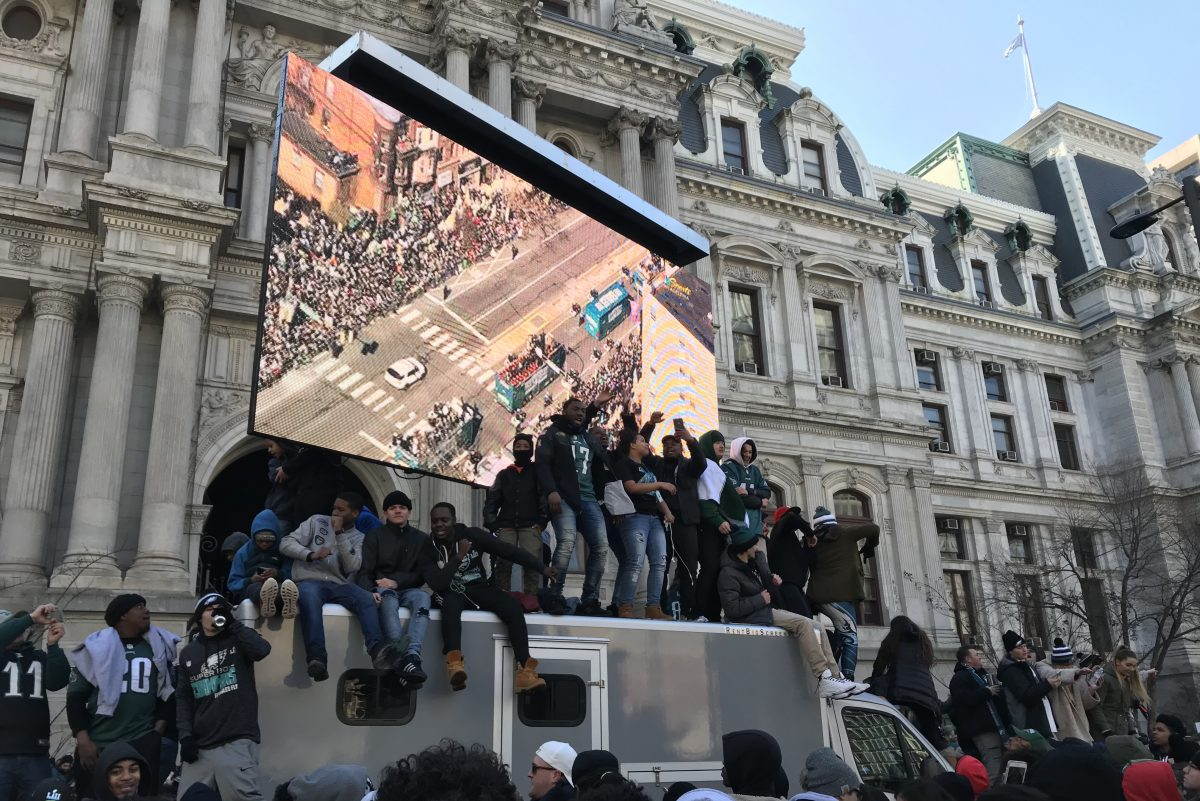 Fans stand on a truck carrying a jumbotron outside City Hall during the Eagles Super Bowl parade.