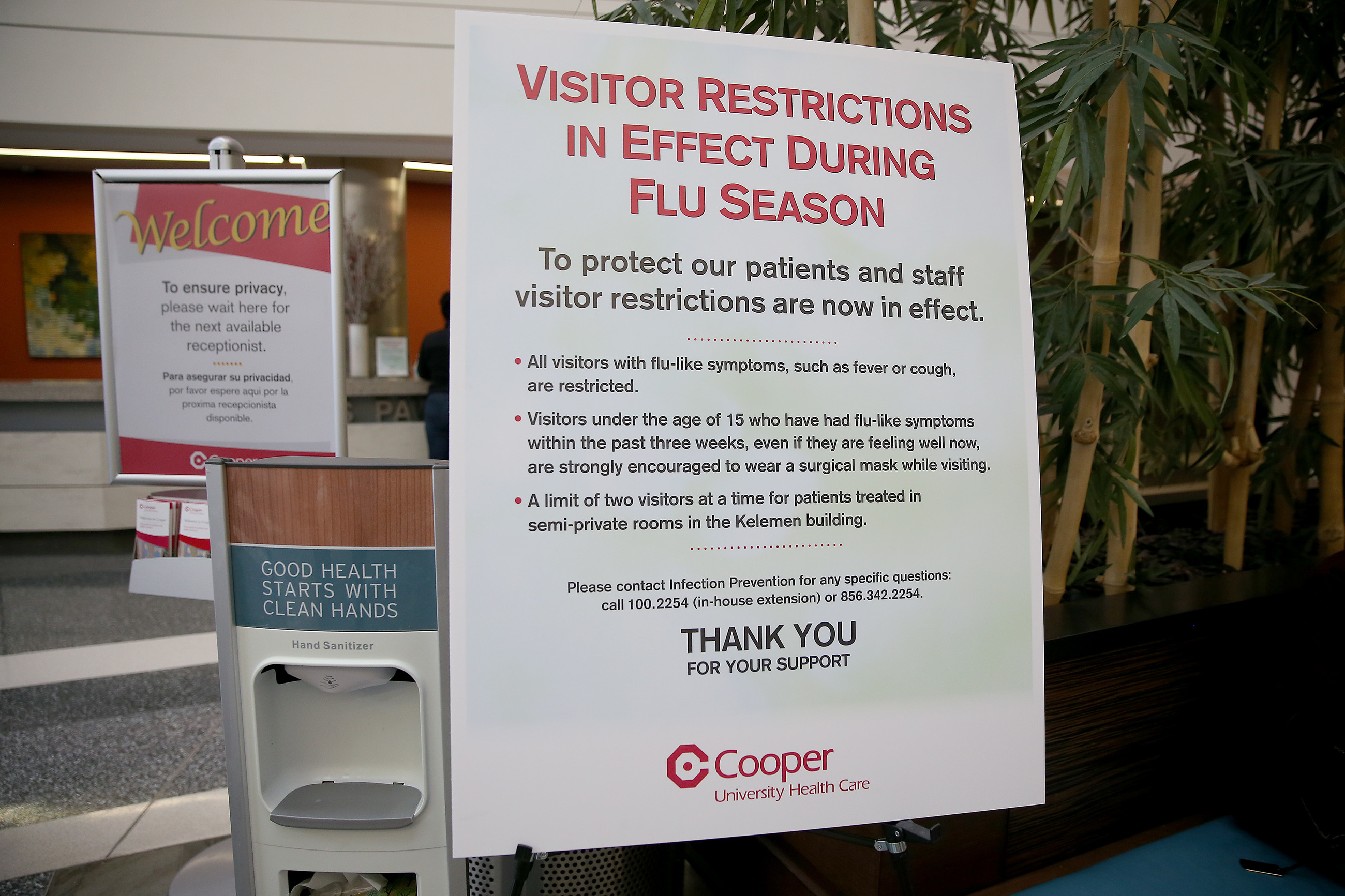 A flu warning sign and a hand sanitizer station now greet visitors in the lobby of Cooper University Hospital in Camden as the hospital deals with an unusually busy flu season.
