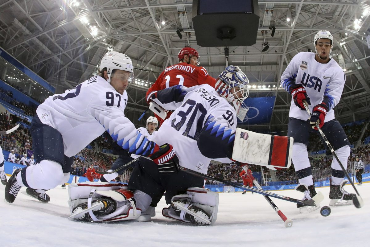 Matt Gilroy (97), goalie Ryan Zapolski (30) and Jordan Greenway (18), of the United States, reach for the puck during the first period of the preliminary round of the men's hockey game against the team from Russia at the 2018 Winter Olympics in Gangneung, South Korea, Saturday, Feb. 17, 2018.