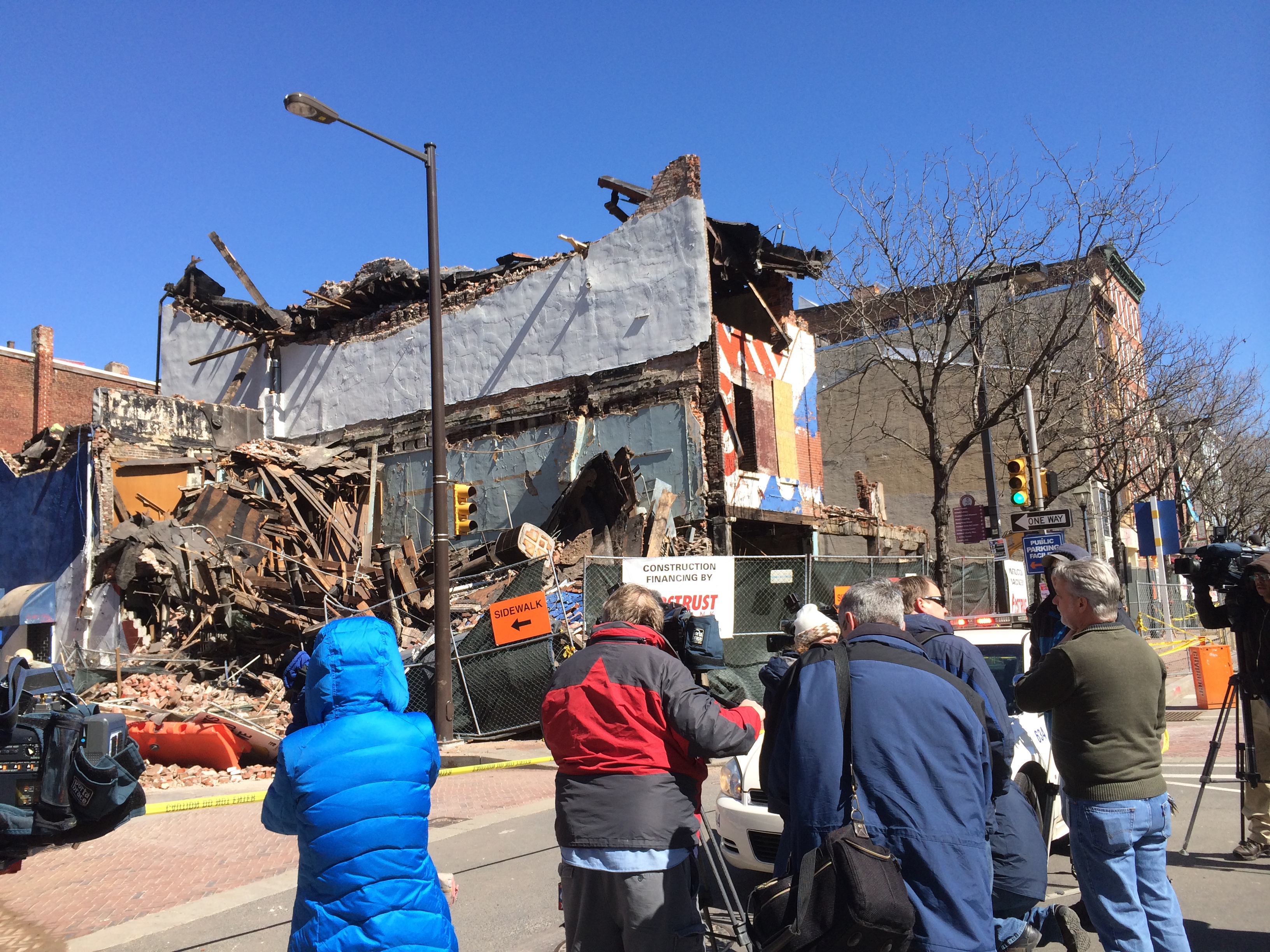 Bystanders look on as the former Shirt Corner at Third and Market is demolished in 2014.
