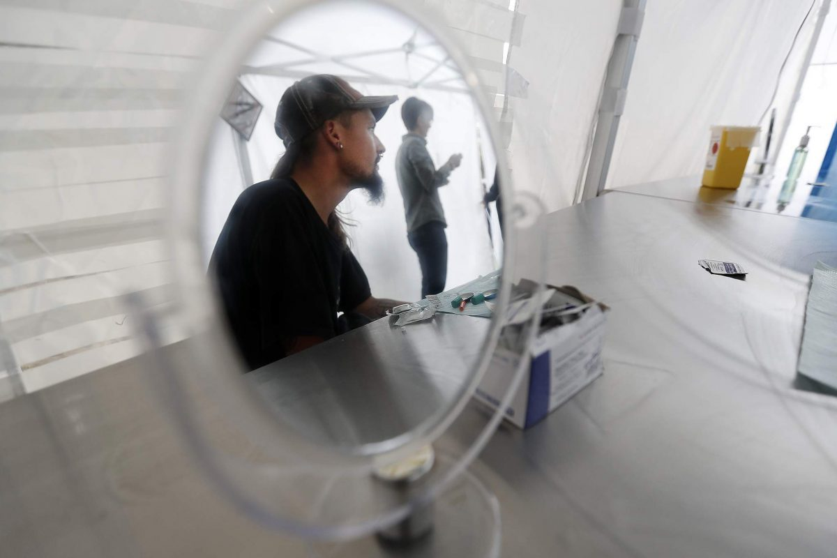 Heroin user Robert Johnson is reflected in a mirror inside the tent at the pop-up safe injection site at Moss Park in Toronto, Canada.