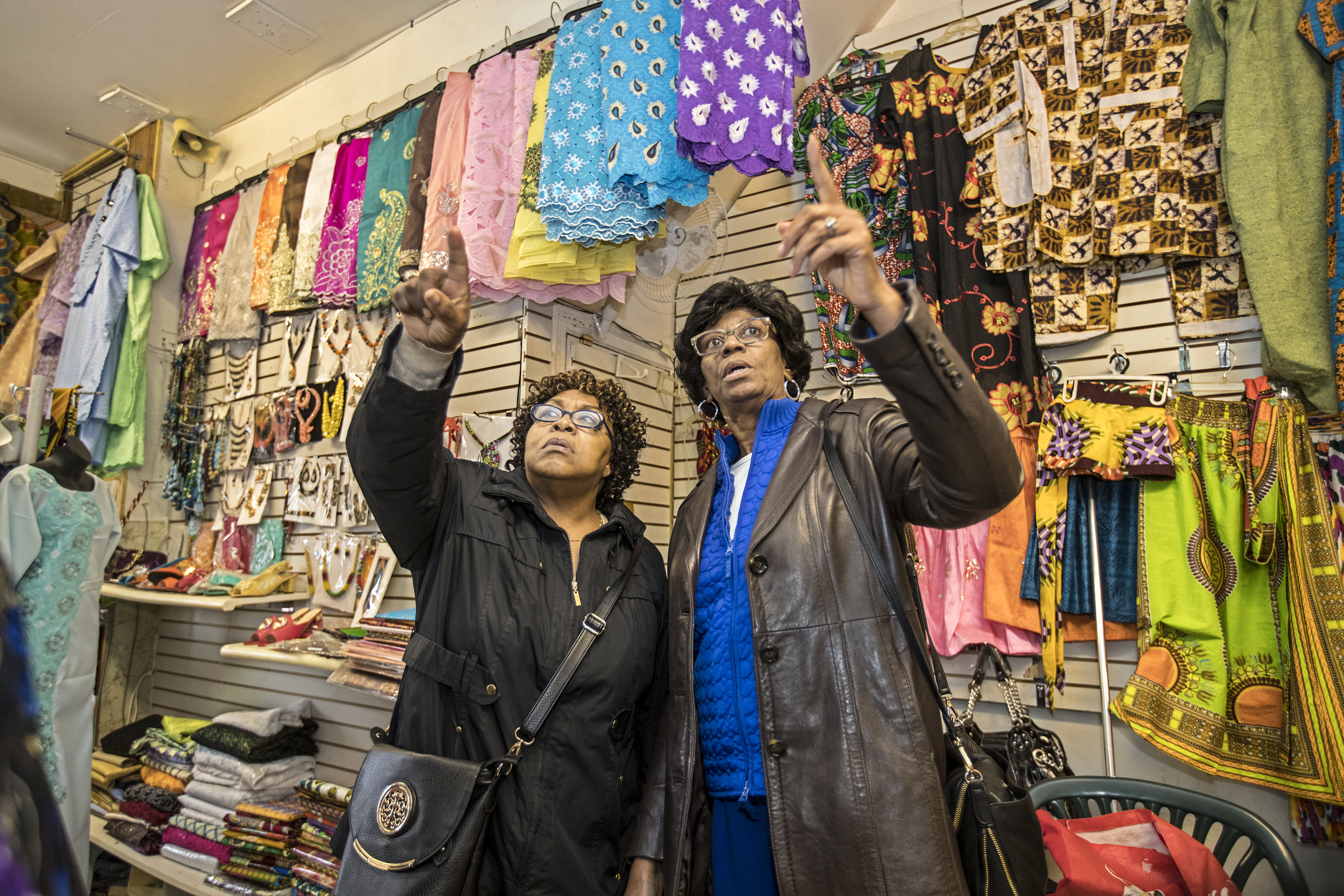Mildred Burden, left, and Dolores Ryans, right, point out African-style dresses they like as they shop at Ngozi African Fashions.
