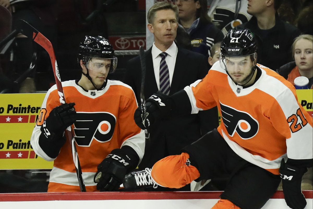 Flyers Head Coach Dave Hakstol watches his team next to center Travis Konecny and center Scott Laughton leaping on the ice against the St. Louis Blues on Saturday, January 6, 2018 in Philadelphia.
