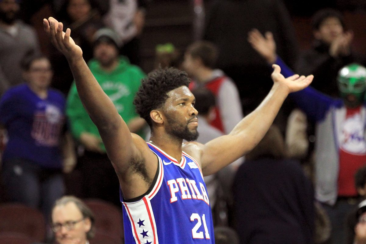 Joel Embiid of the Sixers raises his arms as he leaves the game in the final minute.