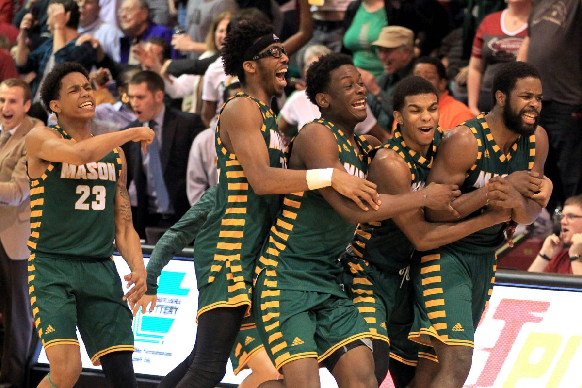 Ian Boyd, right, of George Mason is swarmed by teammates after hitting the game-winning 3-pointer at the buzzer  to defeat St. Joseph's 79-76 at Hagan Arena on Feb.21, 2018.
